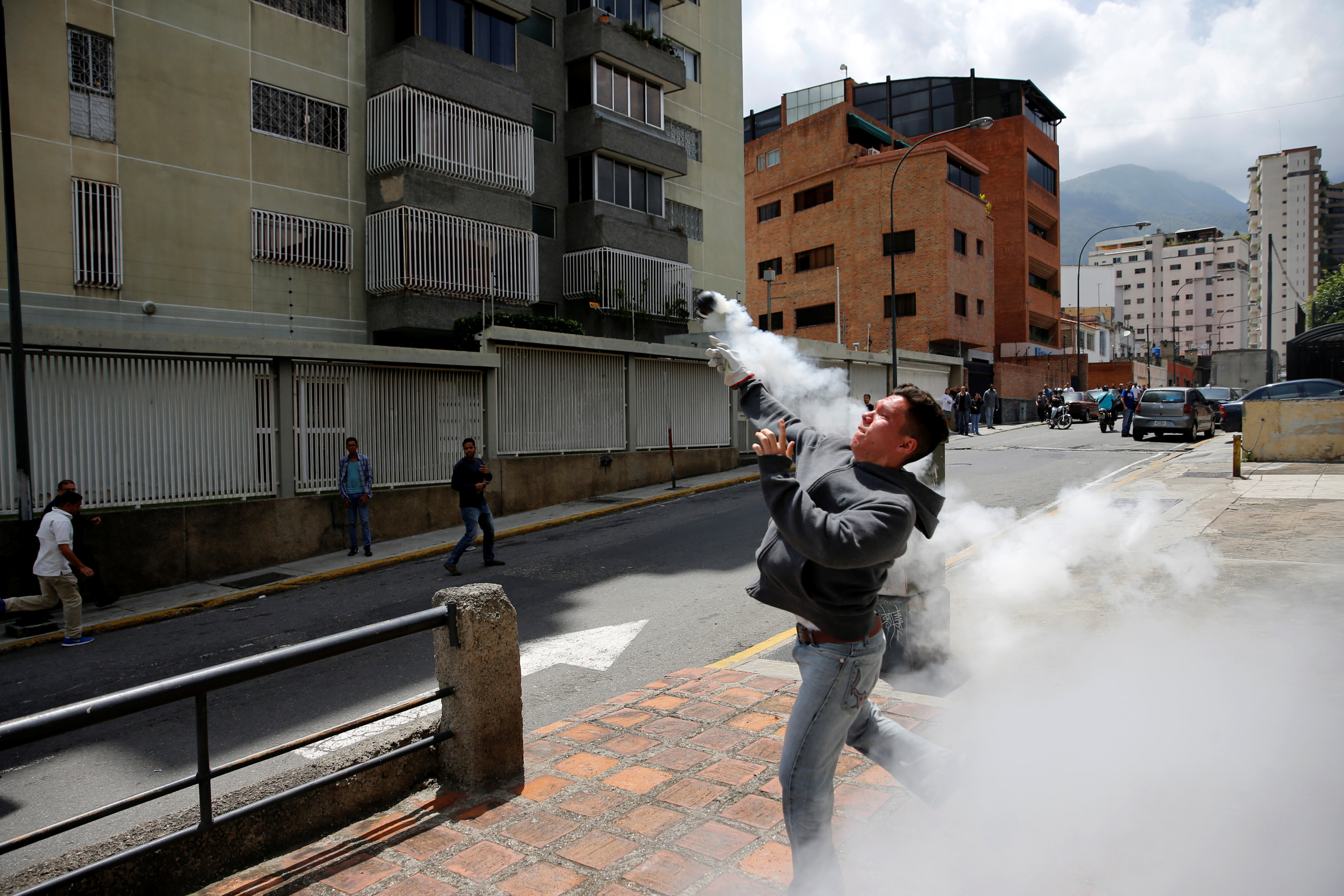 A demonstrator throws back a tear gas grenade while clashing with riot security forces during a rally against Venezuela's President Nicolas Maduro's Government in Caracas, Venezuela June 23, 2017. REUTERS/Ivan Alvarado