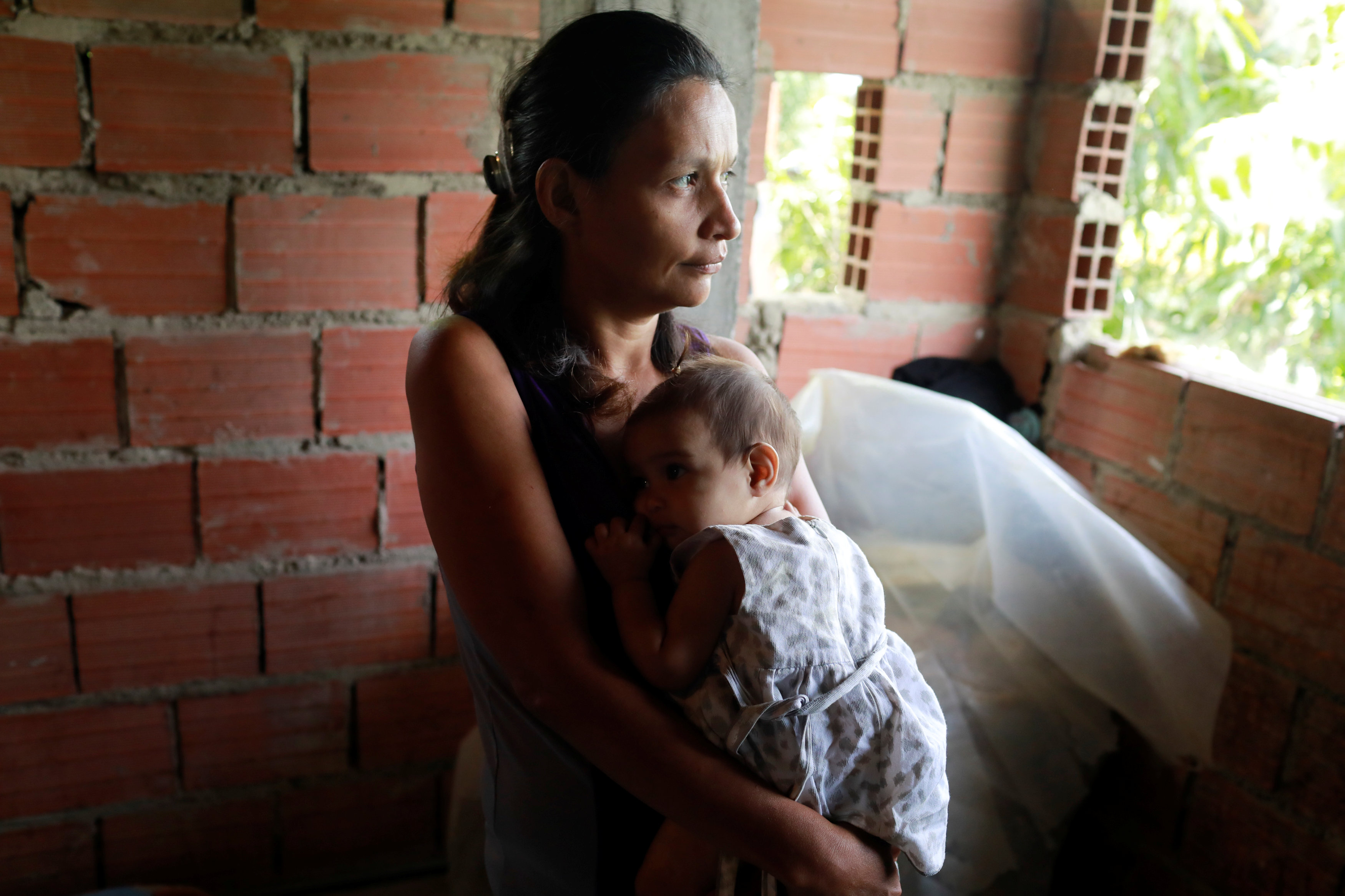 Maryorie Berrios holds Luinyerlin Berrios, who was diagnosed with malnutrition, at her hovel in Caracas, Venezuela June 26, 2017. Picture taken June 26, 2017. REUTERS/Marco Bello