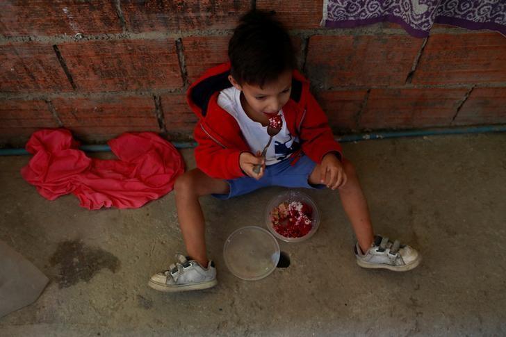 Luis Berrios se sienta en el suelo mientras come su comida en su choza en Caracas, Venezuela. 26 de junio 2017. De la mano de su mamá, Samuel Becerra ingresó a fines de marzo al hospital pediátrico J.M. De Los Ríos, en Caracas, para hacerse una hemodiálisis de rutina. Estando internado, el niño de 12 años contrajo una infección que acabó con su vida, junto a la de otros tres pequeños.REUTERS/Marco Bello - RTS19011