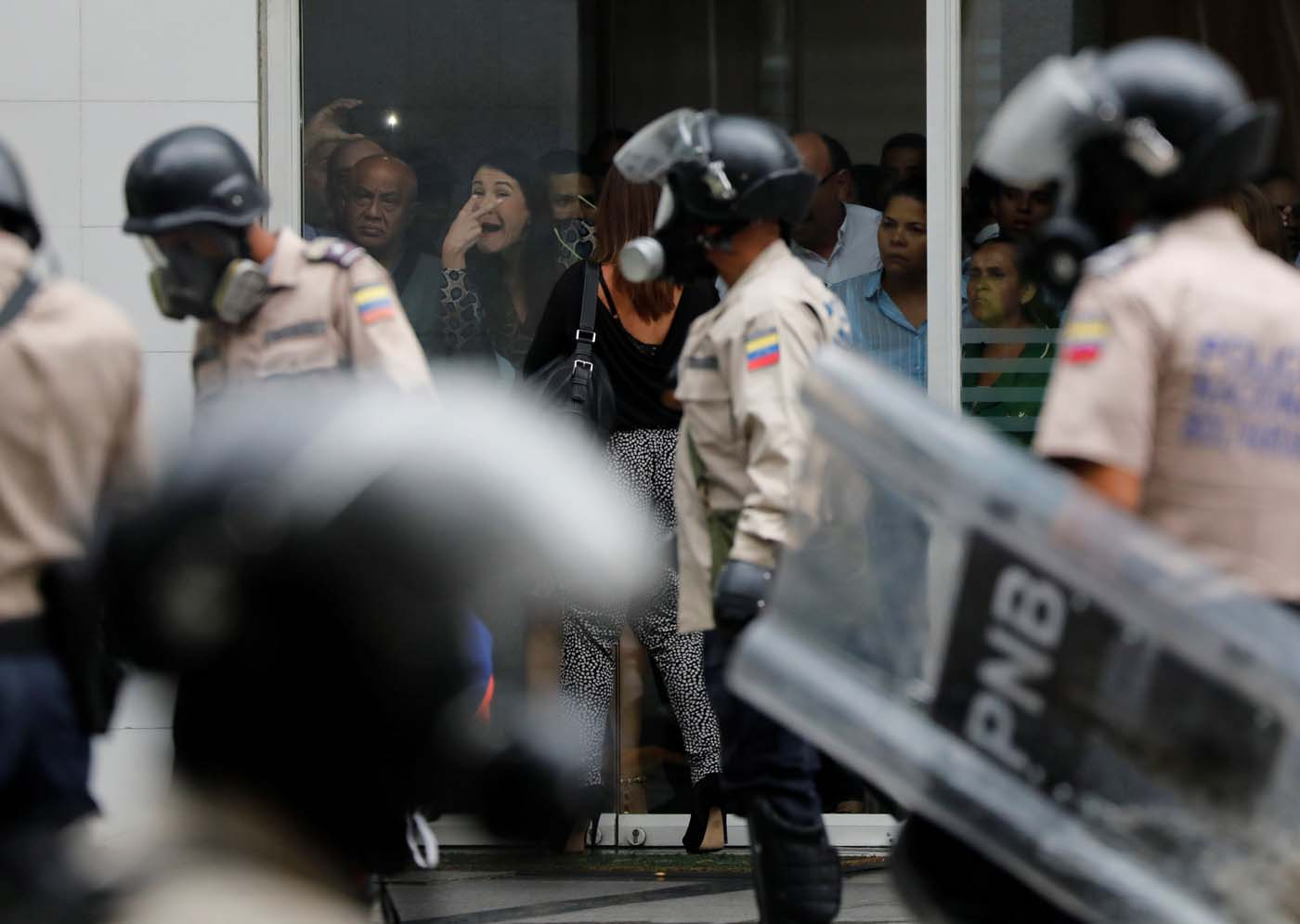 A woman gestures from inside a building as police detain protesters (not pictured) during a rally against Venezuela's President Nicolas Maduro's government in Caracas, Venezuela June 29, 2017. REUTERS/Carlos Garcia Rawlins