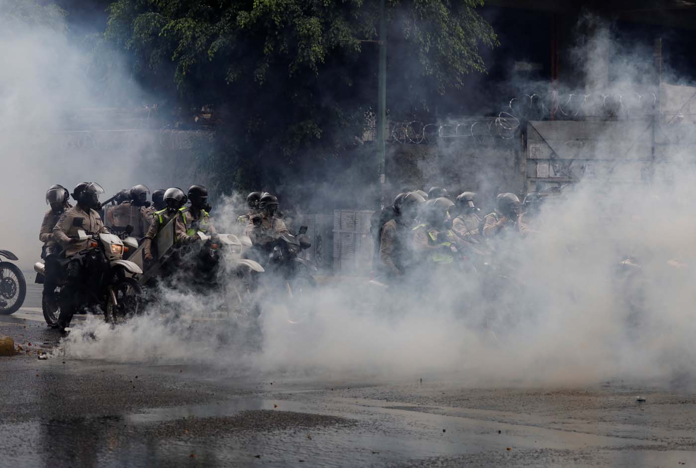 Security forces on motorcycles are seen behind a cloud of tear gas during a rally against Venezuela's President Nicolas Maduro's government in Caracas, Venezuela June 29, 2017. REUTERS/Carlos Garcia Rawlins