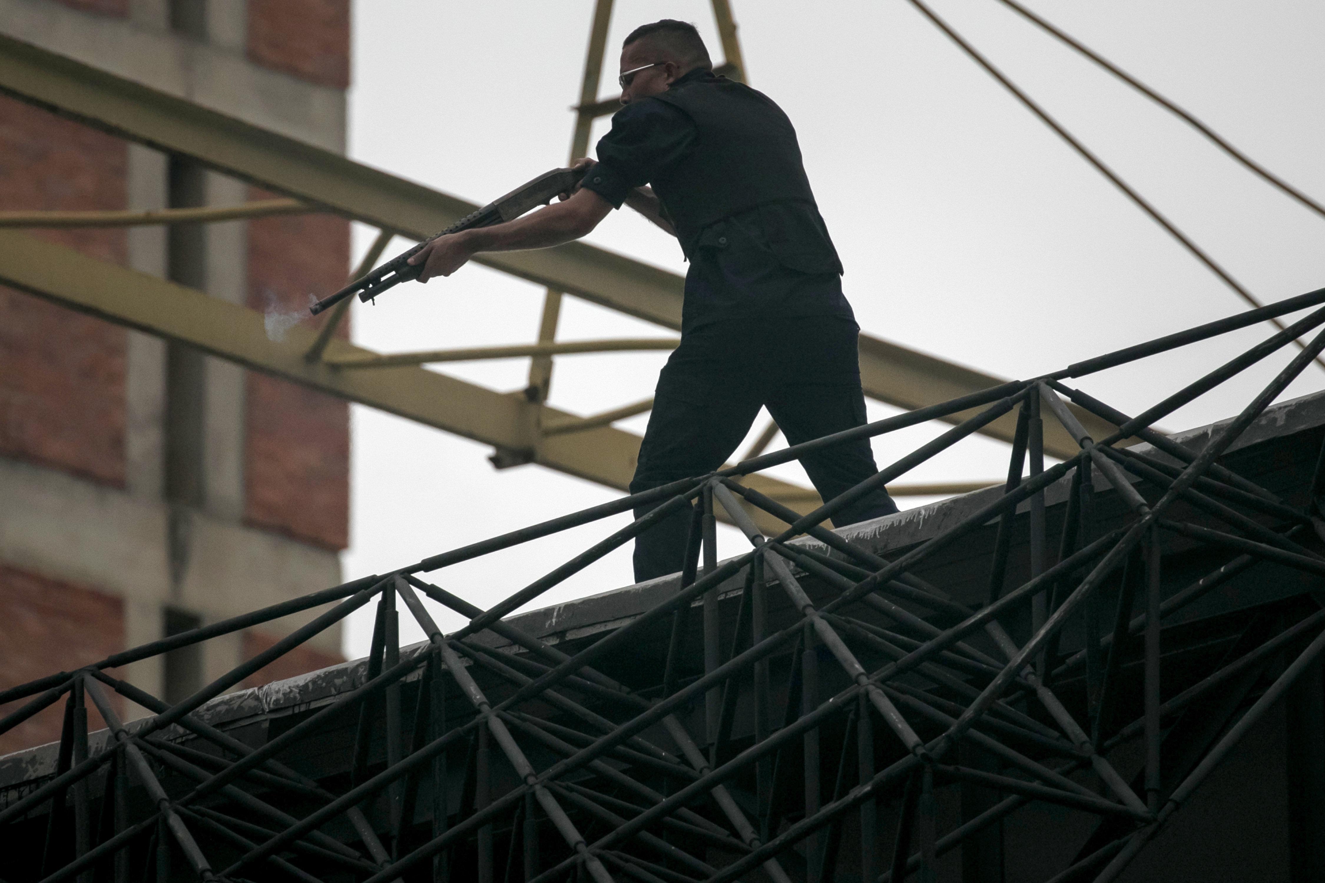 CAR023 CARACAS (VENEZUELA), 07/06/2017.- Un hombre armado permanece en un techo durante una manifestación opositora hoy, miércoles 7 de junio de 2017, en Caracas (Venezuela). Agentes de la fuerza pública venezolana dispersaron hoy con gases lacrimógenos varias de las manifestaciones convocadas en el país por la oposición hacia las sedes del Poder Electoral para protestar por el eventual cambio de Constitución que impulsa el Gobierno. EFE/MIGUEL GUTIÉRREZ