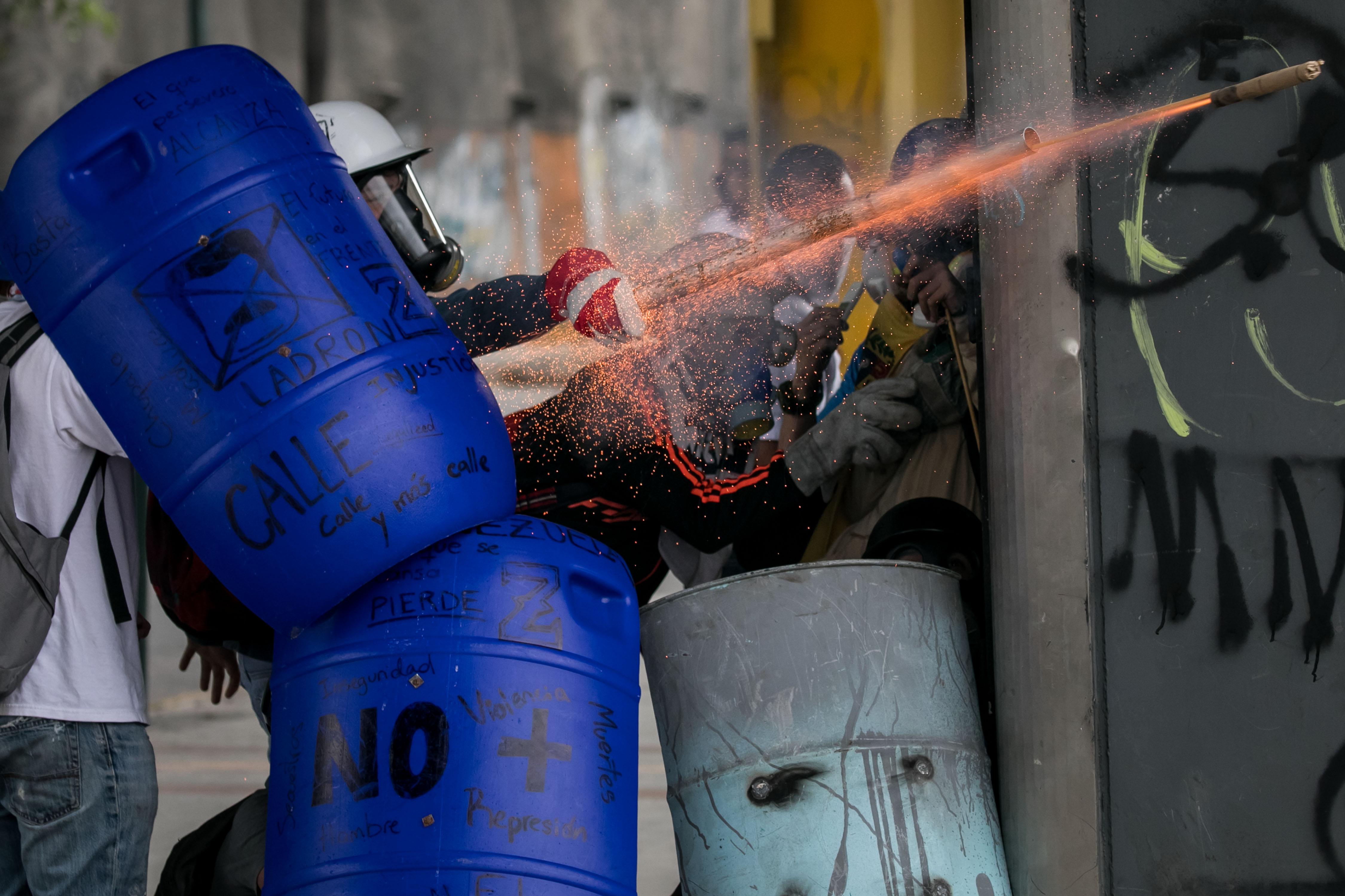 -FOTODELDIA- CAR019 CARACAS (VENEZUELA), 07/06/2017.- Venezolanos opositores se enfrentan a la Policía Nacional Bolivariana (PNB) durante una manifestación hoy, miércoles 7 de junio de 2017, en Caracas (Venezuela). Agentes de la fuerza pública venezolana dispersaron hoy con gases lacrimógenos varias de las manifestaciones convocadas en el país por la oposición hacia las sedes del Poder Electoral para protestar por el eventual cambio de Constitución que impulsa el Gobierno. EFE/MIGUEL GUTIÉRREZ