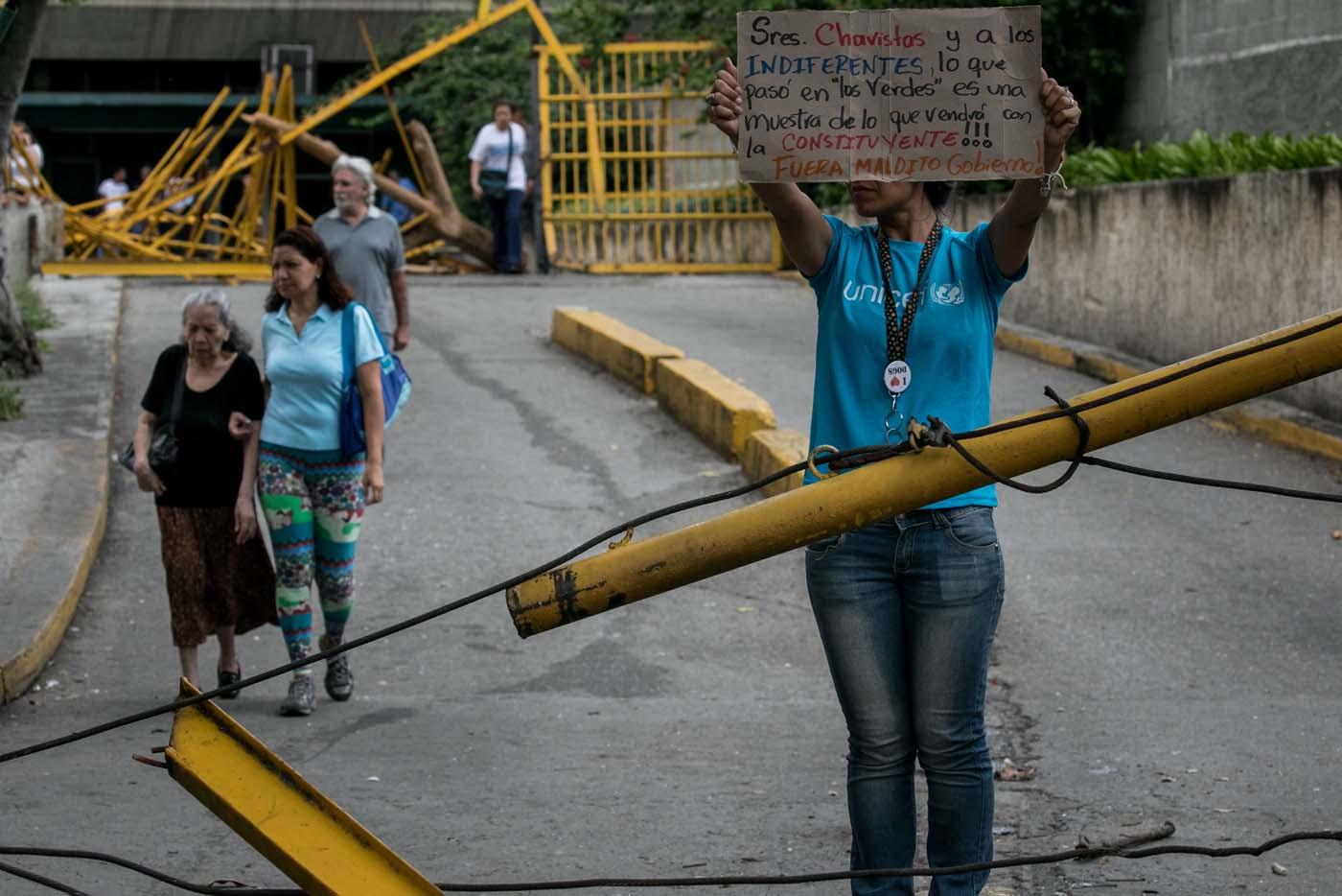 """CAR01. CARACAS (VENEZUELA), 14/06/2017.- Una mujer protesta en la entrada de las residencias Los Verdes ubicadas en el oeste de Caracas (Venezuela) hoy, miércoles 14 de junio de 2017. El oeste de Caracas fue sacudido anoche por la policía militarizada en un operativo que terminó, según el Gobierno venezolano, con la detención de 23 """"terroristas"""" mientras que opositores aseguran hoy que se trató de una acción """"terrible"""" en la que funcionarios causaron destrozos materiales y dispararon a mascotas. EFE/Miguel Gutiérrez"""