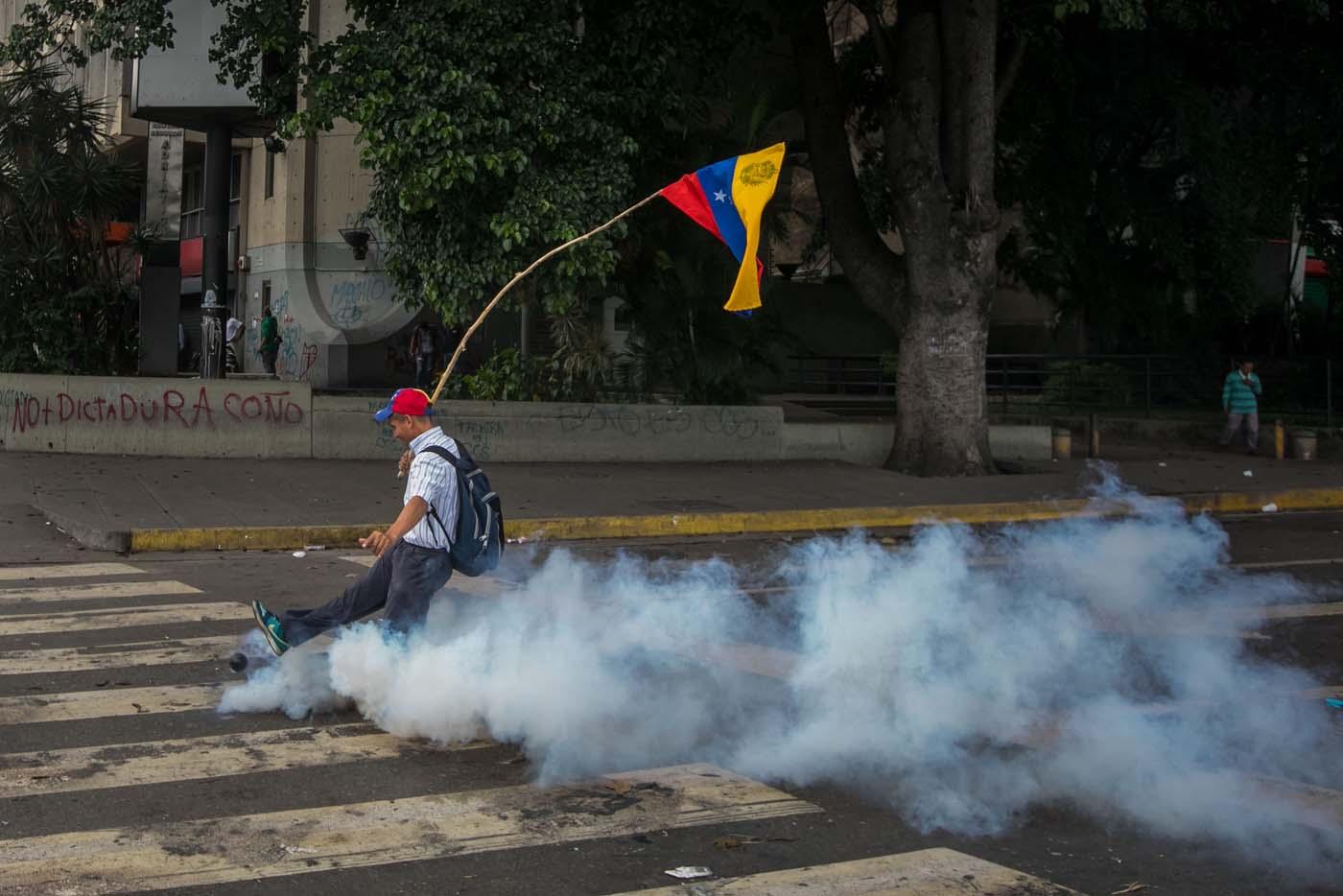 VEN06. CARACAS (VENEZUELA), 14/06/2017.- Un hombre patea una bomba de gas lacrimógeno durante una manifestación hoy, miércoles 14 de junio de 2017, en Caracas (Venezuela). Una concentración de venezolanos opositores al Gobierno de Nicolás Maduro se disolvió hoy en la localidad de Altamira, un bastión del antichavismo en el este de Caracas, luego de que se efectuaran varios disparos en el sitio, constató Efe. EFE/Miguel Gutiérrez