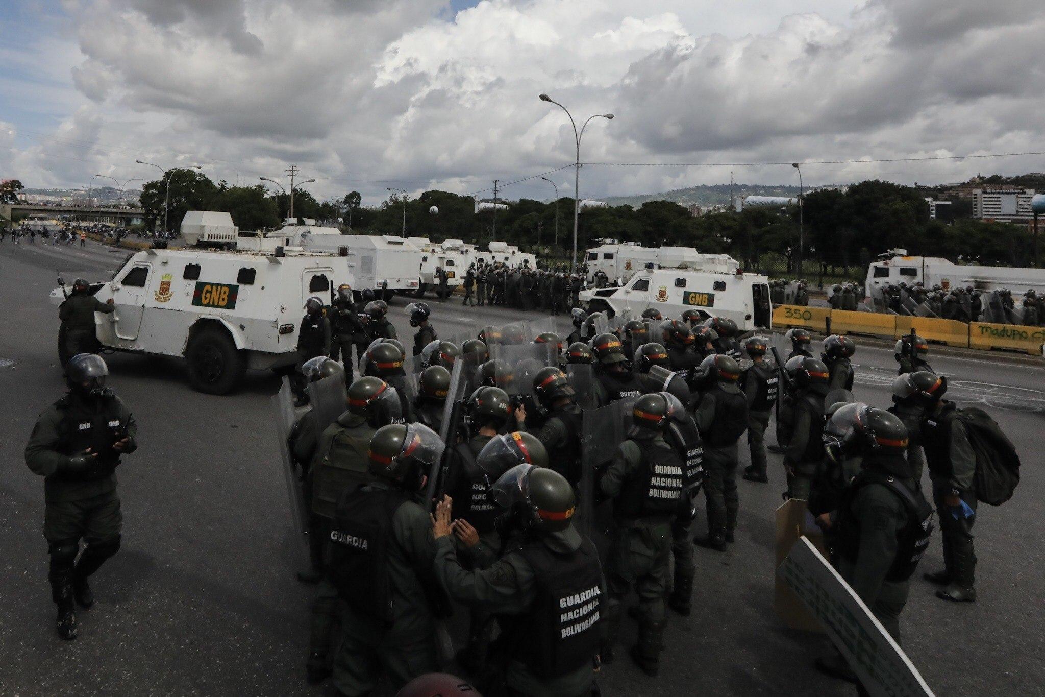 CAR001. CARACAS (VENEZUELA), 19/04/2017.- Miembros de la Guardia Nacional (GNB) intentan detener una manifestación opositora hoy, lunes 19 de junio de 2017, en Caracas (Venezuela). Los cuerpos de seguridad del Estado venezolanos dispersaron hoy con gases lacrimógenos y chorros de agua las marchas de los opositores al Gobierno que salieron desde varios puntos de Caracas e intentaban movilizarse hasta la sede del Consejo Nacional Electoral (CNE), en el centro de la capital. EFE/Miguel Gutiérrez