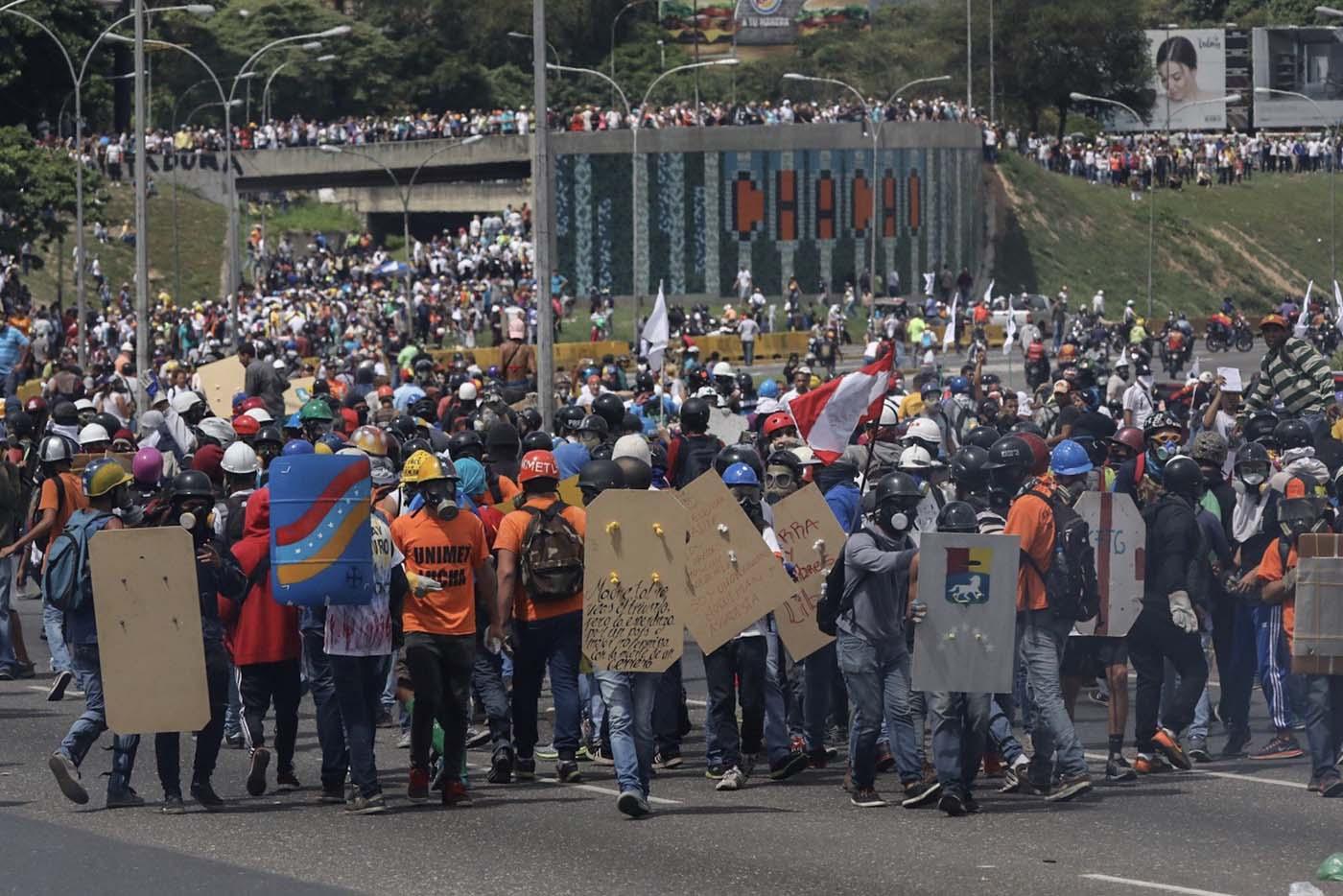CAR001. CARACAS (VENEZUELA), 19/04/2017.- Manifestantes opositores se enfrentan con miembros de la Guardia Nacional (GNB) durante una protesta hoy, lunes 19 de junio de 2017, en Caracas (Venezuela). Los cuerpos de seguridad del Estado venezolanos dispersaron hoy con gases lacrimógenos y chorros de agua las marchas de los opositores al Gobierno que salieron desde varios puntos de Caracas e intentaban movilizarse hasta la sede del Consejo Nacional Electoral (CNE), en el centro de la capital. EFE/Miguel Gutiérrez