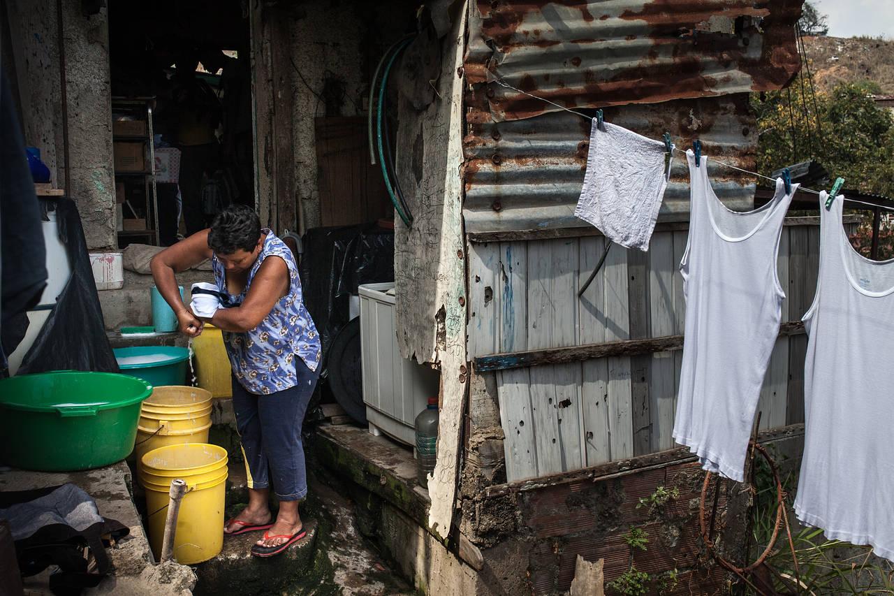 Una mujer lava la ropa en su casa en un barrio pobre de Caracas, 17 de marzo de 2016. El área recibe el servicio regular de agua una vez por semana. FOTO: WIL RIERA PARA THE WALL STREET JOURNAL