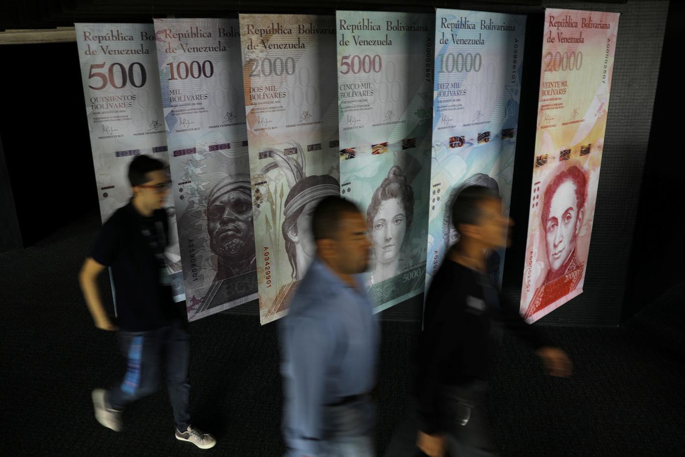 La gente camina cerca de los billetes venezolanos ampliados y exhibidos en el edificio del Banco Central de Venezuela en Caracas, Venezuela. 23 de mayo 2017. La primera subasta del nuevo sistema cambiario de Venezuela, conocido como Dicom, arrojó un tipo de cambio de 2.100 bolívares por dólar, dijo el miércoles el Banco Central. REUTERS/Carlos Barria
