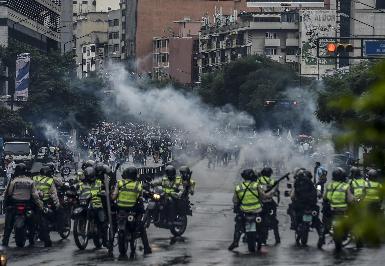 """Los activistas de la oposición chocan con la policía antidisturbios durante una demo en Caracas el 7 de junio de 2017. El jefe del Ejército venezolano, general Vladimir Padrino López, quien también es ministro de Defensa del presidente Nicolas Maduro, está advirtiendo a sus tropas que no cometan """"atrocidades"""" contra los manifestantes que se manifiestan en la mortífera crisis política del país. La advertencia del martes se produjo después de más de dos meses de violentos enfrentamientos entre manifestantes y fuerzas de seguridad. La oposición y un grupo de defensa de prensa dicen que las fuerzas de seguridad han atropellado, atacado y robado a manifestantes y periodistas. / AFP FOTO / JUAN BARRETO"""