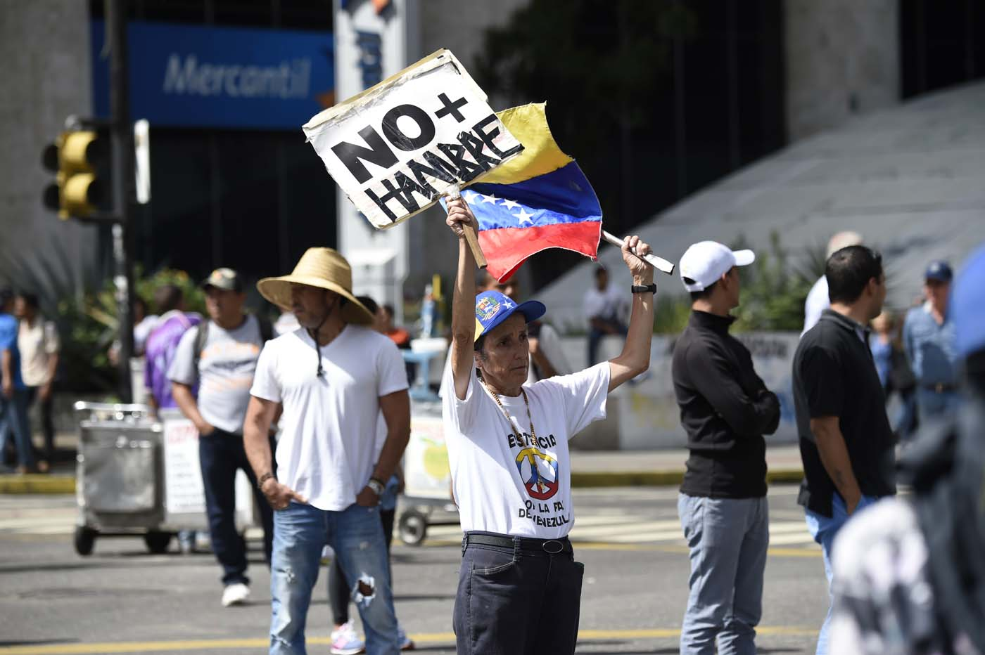 "An opposition activist demonstrating against the government of Venezuelan President Nicolas Maduro holds a placard reading ""No More Hunger"" in Caracas on June 26, 2017. A political and economic crisis in the oil-producing country has spawned often violent demonstrations by protesters demanding Maduro's resignation and new elections. The unrest has left 75 people dead since April 1. / AFP PHOTO / Juan BARRETO"