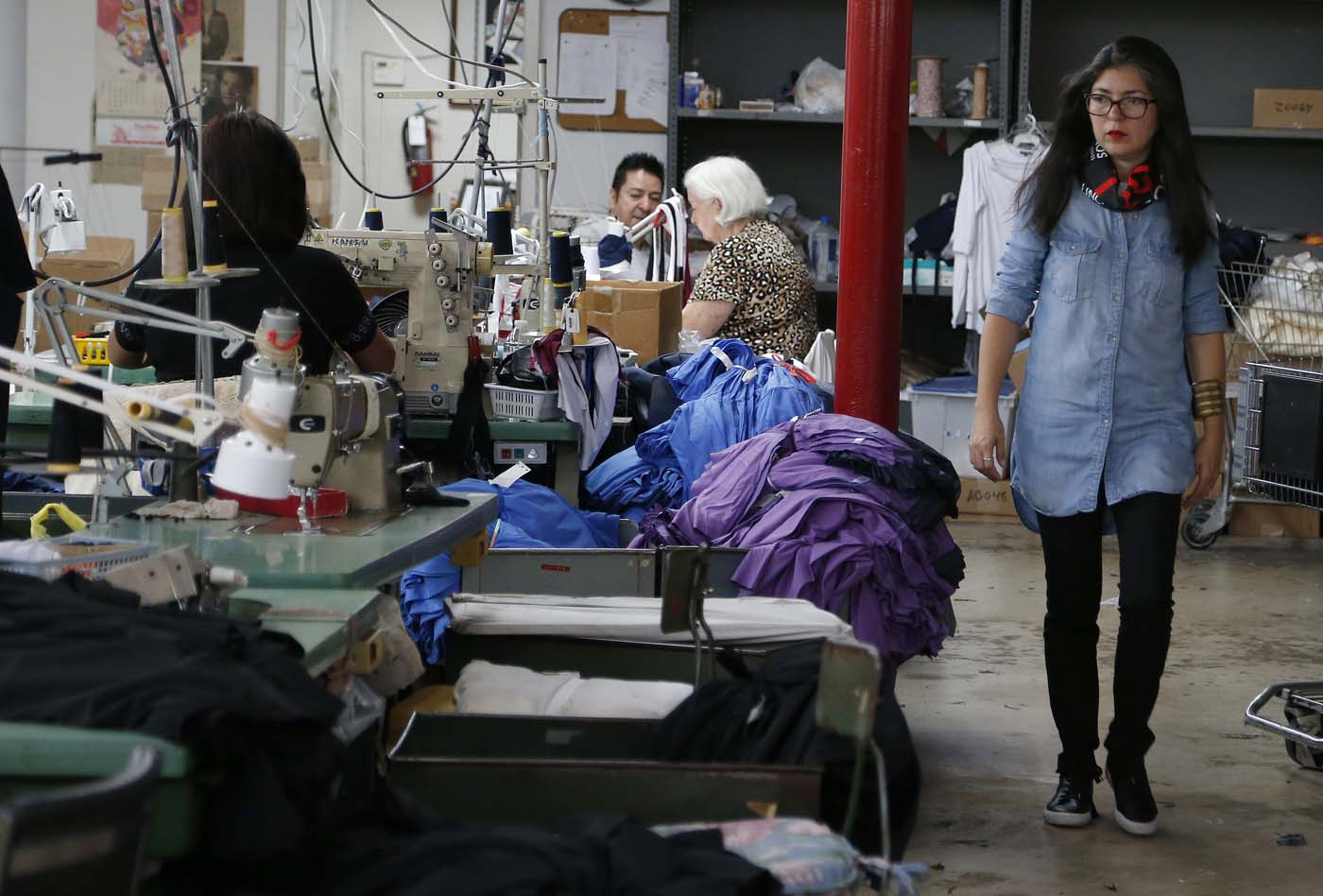 "Venezuelan artist and designer Lisu Vega walks through a warehouse where her clothes for her line ""Resistance"" are being sewn in Miami, Florida on June 8, 2017. The models are dressed in scenes of violence in Caracas and handkerchiefs representing the rags used by protesters to protect themselves from police tear gas. It is the ""Resistance"" collection of Venezuelan fashion designer Lisu Vega. / AFP PHOTO / RHONA WISE"