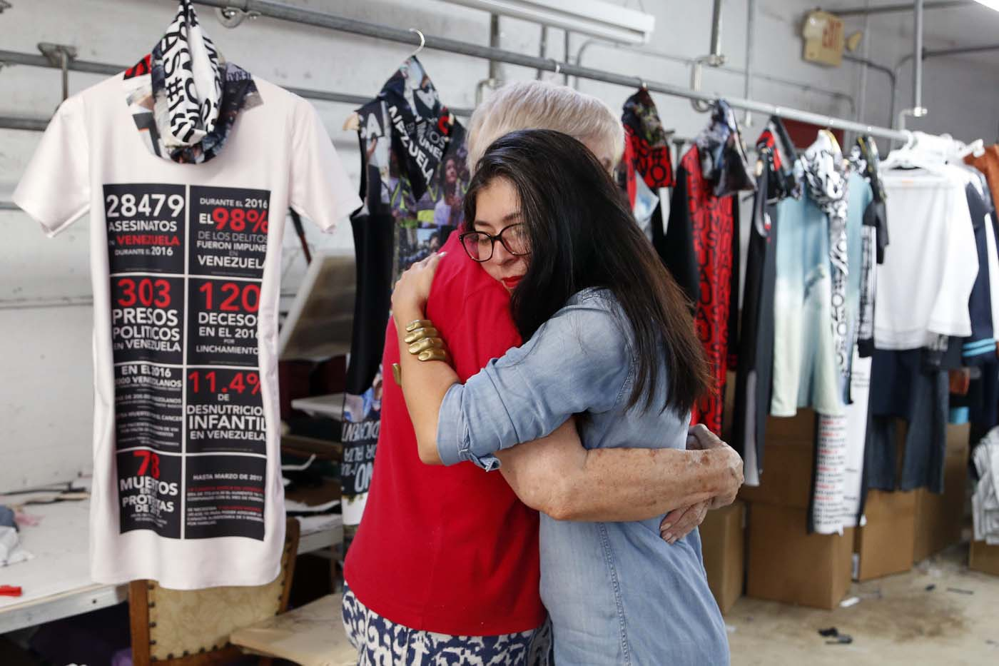"Venezuelan artist and designer Lisu Vega (R) hugs Alexandra Pedrosa (L) in front of her collection ""Resistance"" in a warehouse in Miami, Florida on June 8, 2017. The models are dressed in scenes of violence in Caracas and handkerchiefs representing the rags used by protesters to protect themselves from police tear gas. It is the ""Resistance"" collection of Venezuelan fashion designer Lisu Vega. / AFP PHOTO / RHONA WISE"