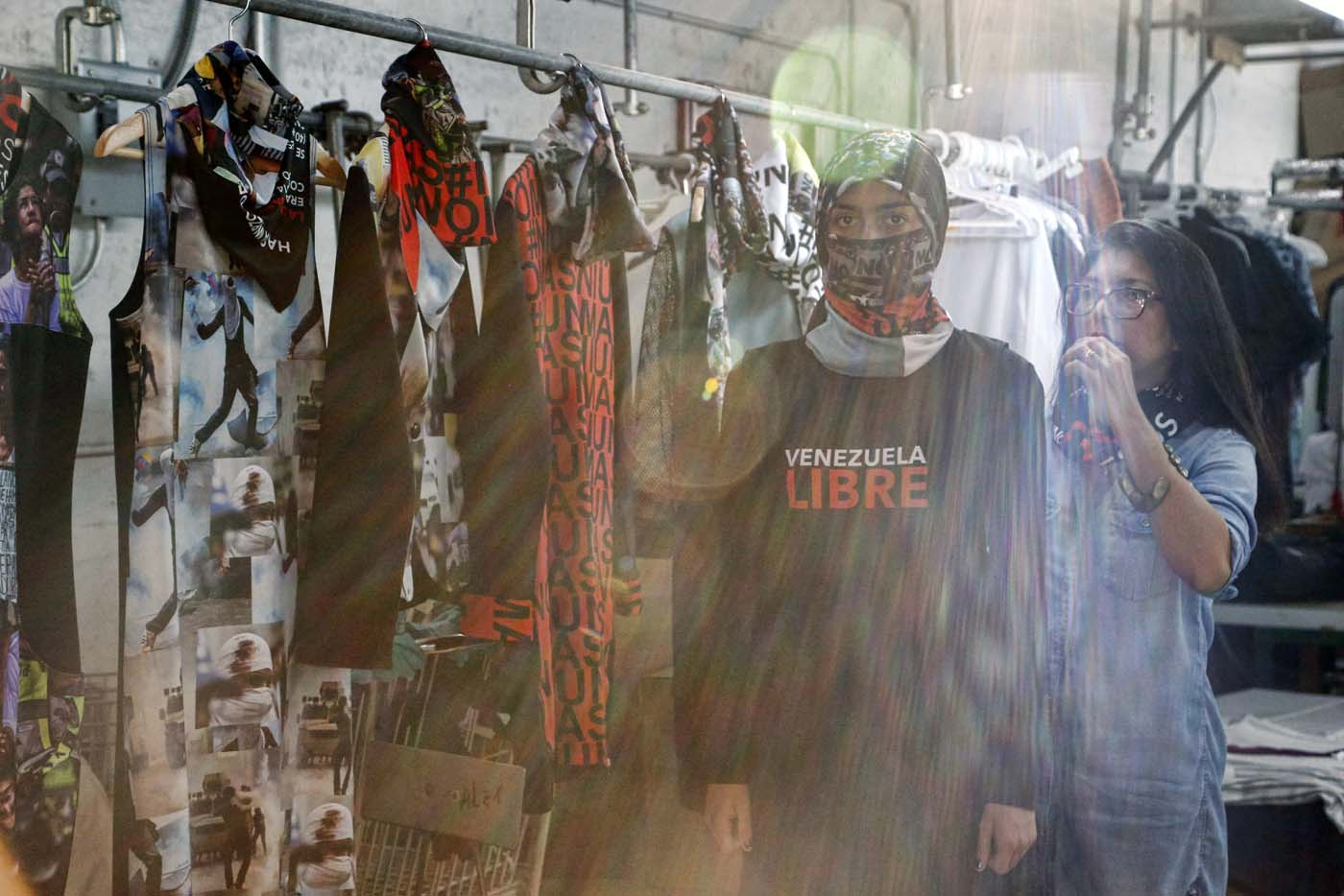 "Sunlight streams through a window as Vida Delgato (L) models clothes by Venezuelan artist and designer Lisu Vega (R) from her collection ""Resistance"" in a warehouse in Miami, Florida on June 8, 2017. The models are dressed in scenes of violence in Caracas and handkerchiefs representing the rags used by protesters to protect themselves from police tear gas. It is the ""Resistance"" collection of Venezuelan fashion designer Lisu Vega. / AFP PHOTO / RHONA WISE"