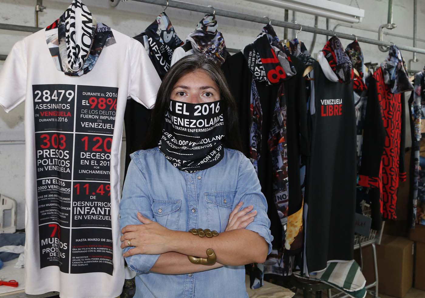 "Venezuelan artist and designer Lisu Vega poses in front of her collection ""Resistance"" in a warehouse in Miami, Florida on June 8, 2017. The models are dressed in scenes of violence in Caracas and handkerchiefs representing the rags used by protesters to protect themselves from police tear gas. It is the ""Resistance"" collection of Venezuelan fashion designer Lisu Vega. / AFP PHOTO / RHONA WISE"