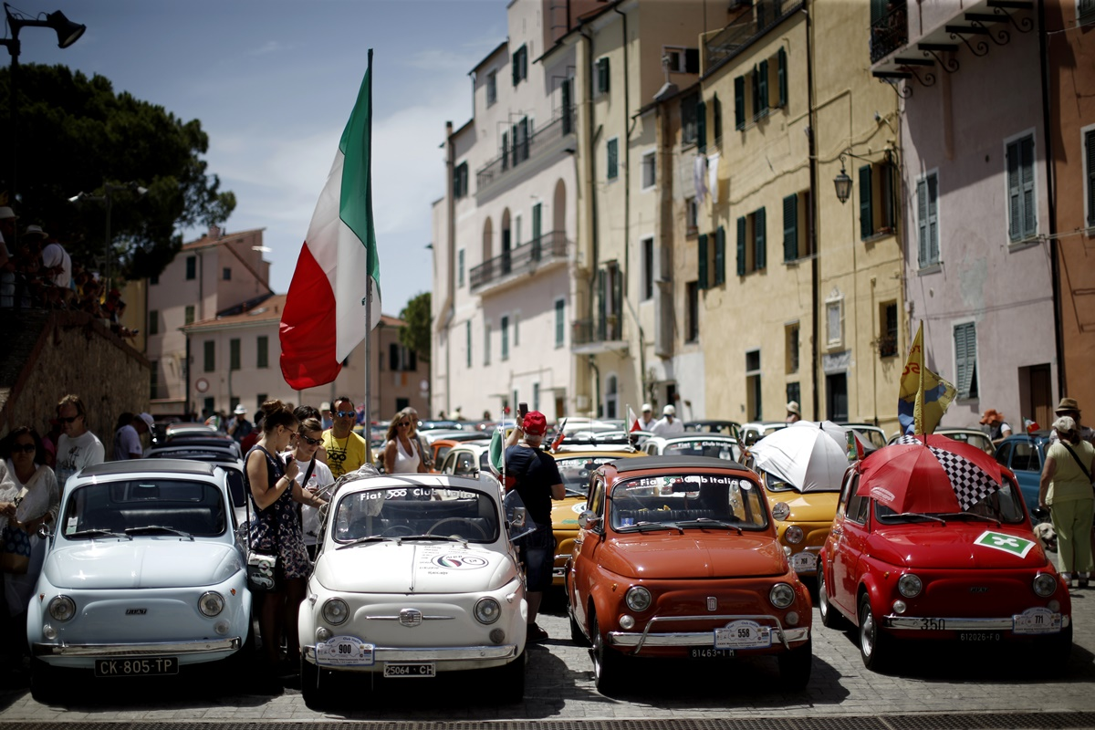 People take part at the 34th International Rally of Fiat 500 Club Italia for the 60th anniversary of this car on July 8, 2017, in Garlenda, near Genoa.   More than 1200 cars came from Europe to take part at the 34 rally of Garlenda to celebrate the 60th anniversary of the Fiat 500.  / AFP PHOTO / Marco BERTORELLO