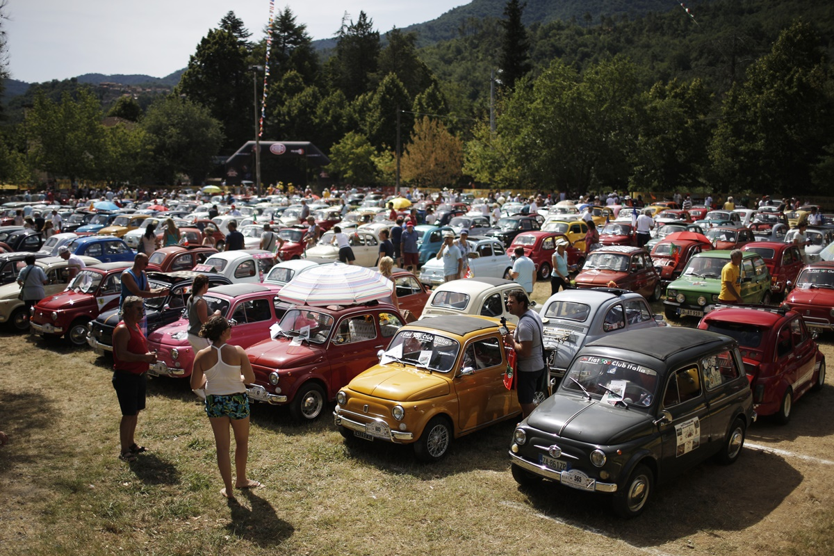 People take part in the 34th International Rally of Fiat 500 Club Italia for the 60th anniversary of this car on July 8, 2017, in Garlenda, near Genoa.   More than 1200 cars came from Europe to take part at the 34 rally of Garlenda to celebrate the 60th anniversary of the Fiat 500.  / AFP PHOTO / Marco BERTORELLO