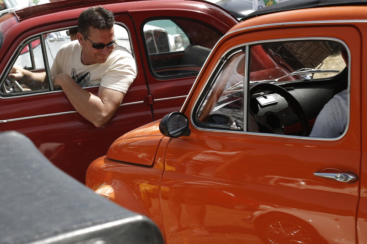 An enthusiast looks on during the 34th International Rally of Fiat 500 Club Italia for the 60th anniversary of this car on July 8, 2017, in Garlenda, near Genoa.   More than 1200 cars came from Europe to take part at the 34 rally of Garlenda to celebrate the 60th anniversary of the Fiat 500.  / AFP PHOTO / Marco BERTORELLO