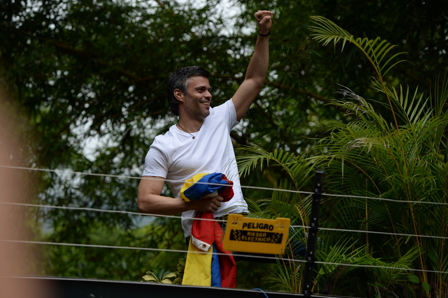 "Venezuelan opposition leader Leopoldo Lopez greets supporters gathering outside his house in Caracas, after he was released from prison and placed under house arrest for health reasons, on July 8, 2017. Venezuela's Supreme Court confirmed on its Twitter account it had ordered Lopez to be moved to house arrest, calling it a ""humanitarian measure"" granted on July 7 by the court's president Maikel Moreno. ""Leopoldo Lopez is at his home in Caracas with (wife) Lilian and his children,"" Lopez's Spanish lawyer Javier Cremades said in Madrid. ""He is not yet free but under house arrest. He was released at dawn."" / AFP PHOTO / Federico PARRA"