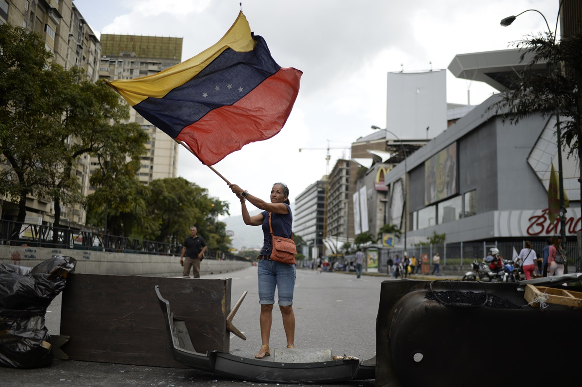 Venezuelan opposition activists protest in Caracas on July 10, 2017. Venezuela hit its 100th day of anti-government protests Sunday, amid uncertainty over whether the release from prison a day earlier of prominent political prisoner Leopoldo Lopez might open the way to negotiations to defuse the profound crisis gripping the country. / AFP PHOTO / FEDERICO PARRA