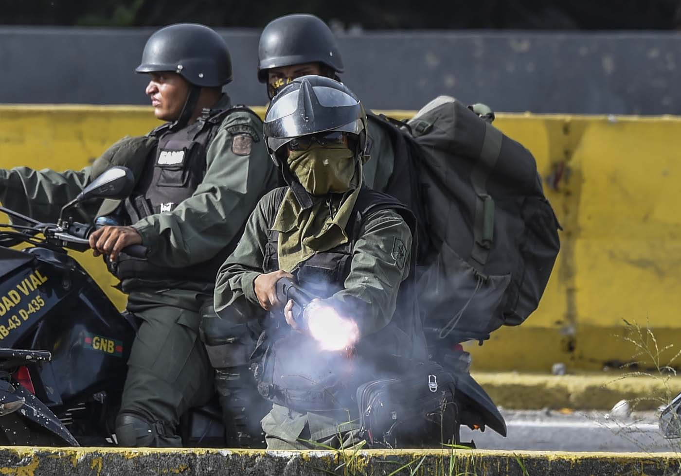 Members of the National Guard charge on opposition activists during protests against Venezuelan President Nicolas Maduro in Caracas on July 10, 2017. Venezuela hit its 100th day of anti-government protests Sunday, amid uncertainty over whether the release from prison a day earlier of prominent political prisoner Leopoldo Lopez might open the way to negotiations to defuse the profound crisis gripping the country. / AFP PHOTO / JUAN BARRETO