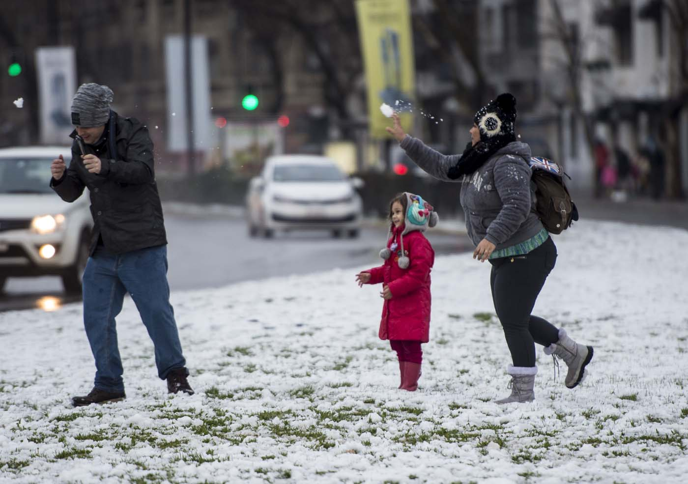 People play with snow in Santiago on July 15, 2017.  An unusual snowfall --the first of such intensity since 2007-- surprised the inhabitants of the Chilean capital, causing a few power cuts and minor traffic jams, in particular in the eastern areas of the capital, the closest to the Andes mountain range. / AFP PHOTO / Martin BERNETTI