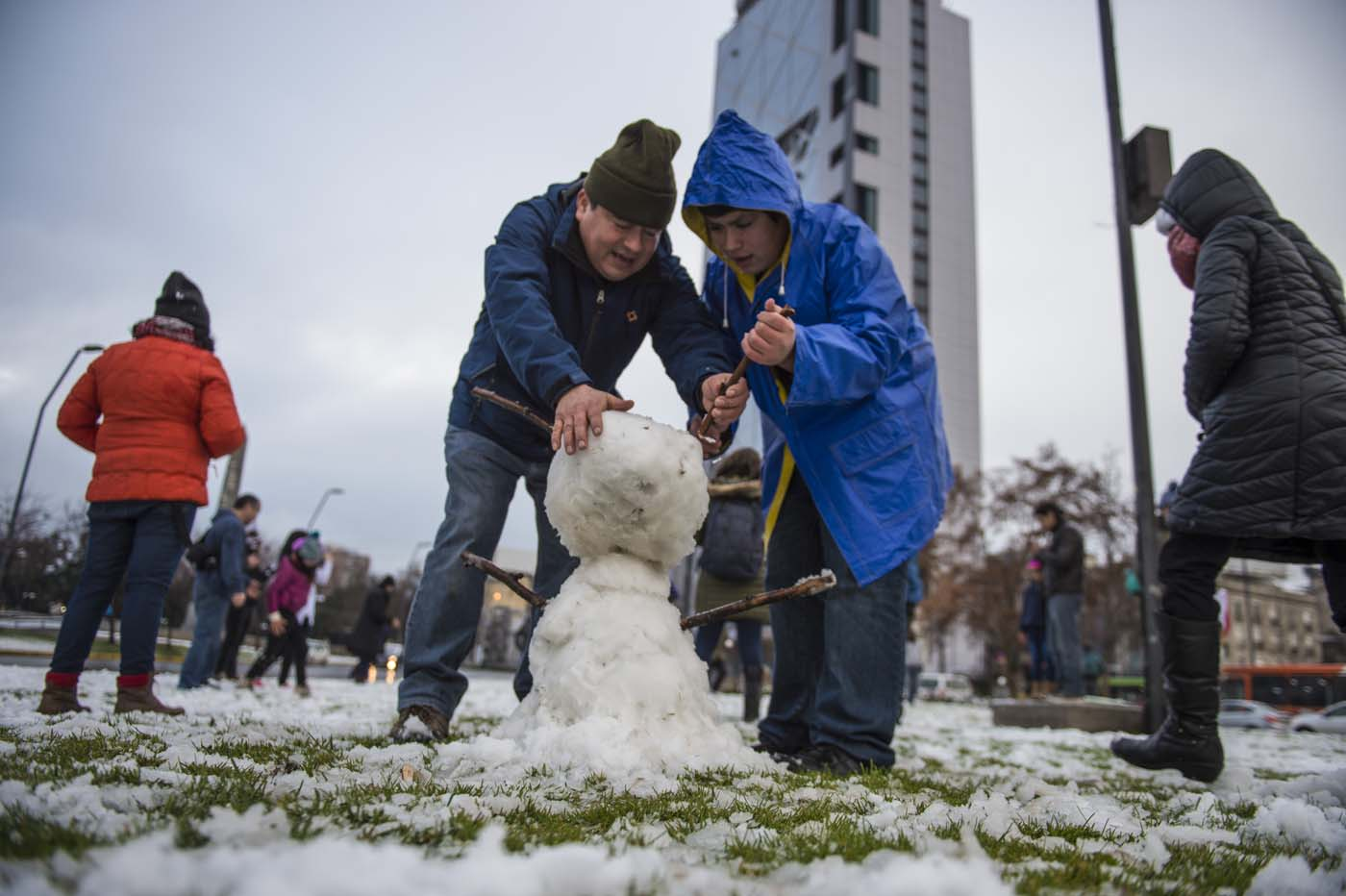 People make a snowman in Santiago on July 15, 2017.  An unusual snowfall --the first of such intensity since 2007-- surprised the inhabitants of the Chilean capital, causing a few power cuts and minor traffic jams, in particular in the eastern areas of the capital, the closest to the Andes mountain range. / AFP PHOTO / Martin BERNETTI