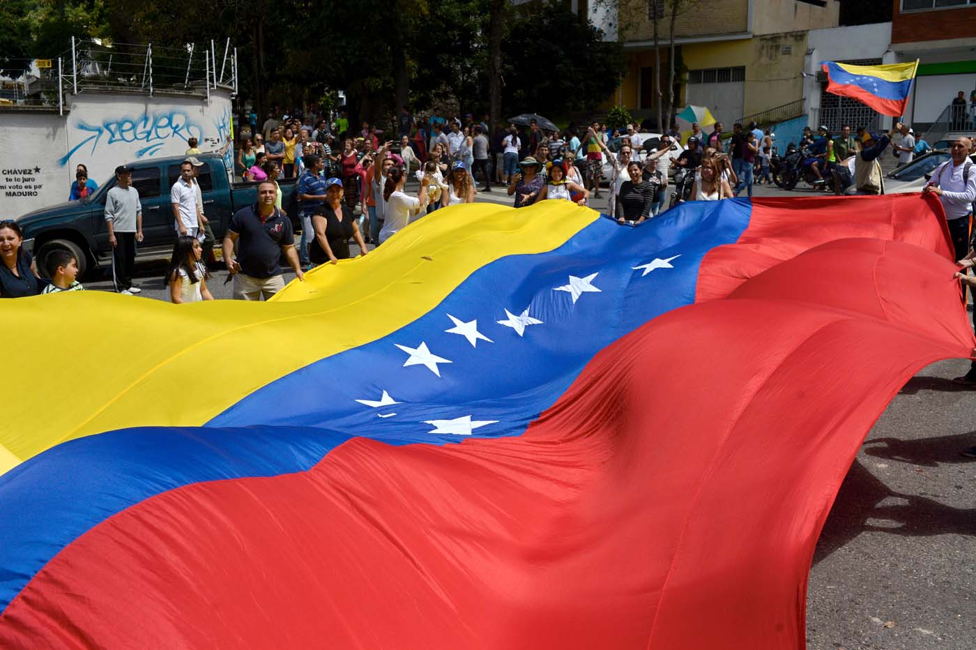 People gather in Caracas on July 16, 2017 during an opposition-organized vote to measure public support for President Nicolas Maduro's plan to rewrite the constitution. Authorities have refused to greenlight the vote that has been presented as an act of civil disobedience and supporters of Maduro are boycotting it. Protests against Maduro since April 1 have brought thousands to the streets demanding elections, but has also left 95 people dead, according to an official toll. / AFP PHOTO / FEDERICO PARRA