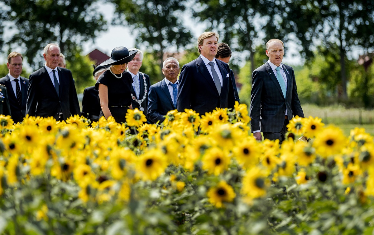 """Dutch King Willem-Alexander (2ndR) and Queen Maxima (3rdL) attend the unveiling of the National Monument for the MH17 victims in Vijfhuizen on July 17, 2017. Three years after Flight MH17 was shot down by a missile over war-torn Ukraine, more than 2,000 relatives gather to unveil a """"living memorial"""" to their loved ones. A total of 298 trees have been planted in the shape of a green ribbon, one for each of the victims who died on board the Malaysia Airlines flight en route from Amsterdam to Kuala Lumpur. The flowers also represent """"the sunflower fields in eastern Ukraine where some parts of the plane wreckage were found"""". / AFP PHOTO / ANP / Remko de Waal / Netherlands OUT"""