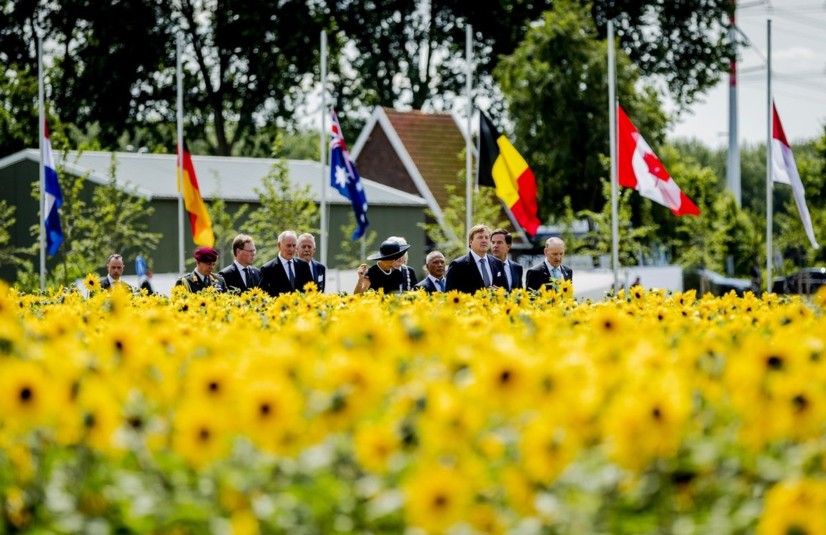 """Dutch King Willem-Alexander (3rdR) and Queen Maxima (C) attend the unveiling of the National Monument for the MH17 victims in Vijfhuizen on July 17, 2017. Three years after Flight MH17 was shot down by a missile over war-torn Ukraine, more than 2,000 relatives gather to unveil a """"living memorial"""" to their loved ones. A total of 298 trees have been planted in the shape of a green ribbon, one for each of the victims who died on board the Malaysia Airlines flight en route from Amsterdam to Kuala Lumpur. The flowers also represent """"the sunflower fields in eastern Ukraine where some parts of the plane wreckage were found"""". / AFP PHOTO / ANP / Remko de Waal / Netherlands OUT"""