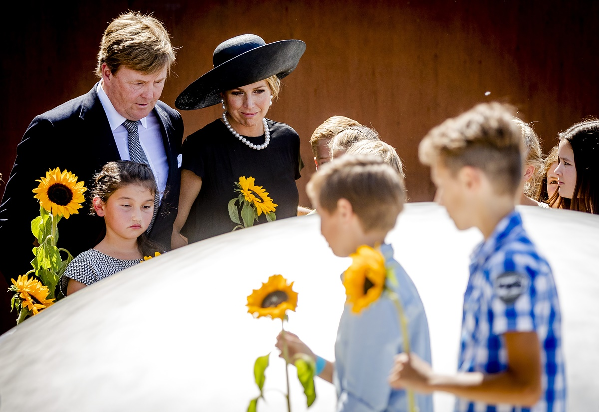 """Dutch King Willem-Alexander (L) and Queen Maxima (C) attend the unveiling of the National Monument for the MH17 victims in Vijfhuizen on July 17, 2017. Three years after Flight MH17 was shot down by a missile over war-torn Ukraine, more than 2,000 relatives gather to unveil a """"living memorial"""" to their loved ones. A total of 298 trees have been planted in the shape of a green ribbon, one for each of the victims who died on board the Malaysia Airlines flight en route from Amsterdam to Kuala Lumpur. The flowers also represent """"the sunflower fields in eastern Ukraine where some parts of the plane wreckage were found"""". / AFP PHOTO / ANP / Remko de Waal / Netherlands OUT"""