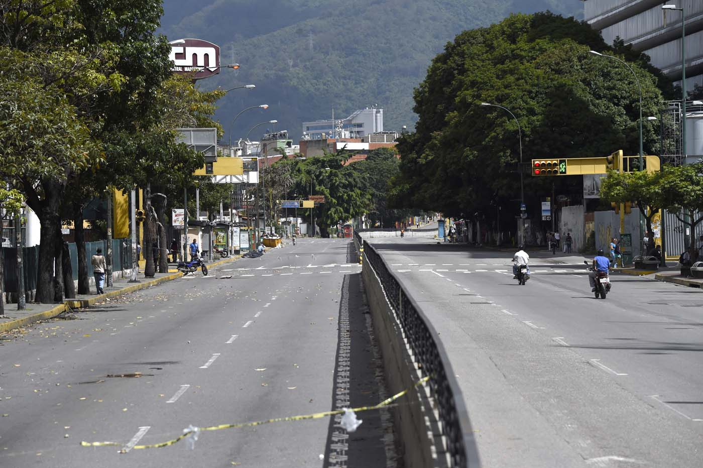An avenue looks void of vehicles during a general strike in Caracas, on July 20, 2017. A 24-hour nationwide strike got underway in Venezuela Thursday, in a bid by the opposition to increase pressure on beleaguered leftist President Nicolas Maduro following four months of deadly street demonstrations. / AFP PHOTO / JUAN BARRETO