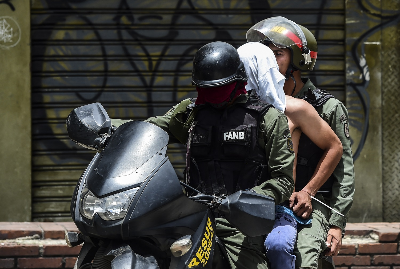 Los motociclistas de la Guardia Nacional llevan a un manifestante arrestado bajo custodia durante una protesta contra el gobierno en Caracas, el 20 de julio de 2017. Una huelga nacional de 24 horas se inició en Venezuela el jueves, en un intento de la oposición de aumentar la presión sobre el presionado presidente izquierdista Nicolás Maduro tras cuatro meses de manifestaciones callejeras mortales. / AFP PHOTO / RONALDO SCHEMIDT