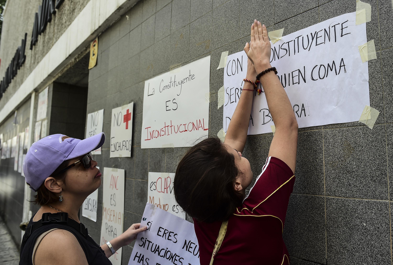 Las mujeres pegan letreros contra el presidente Maduro y su llamado a la Asamblea Constituyente en la pared de una escuela que será utilizada como mesa de votación, en Caracas, el 24 de julio de 2017. La enojada oposición venezolana está presionando por un boicot de una próxima votación que rechaza como una estratagema del presidente Nicolas Maduro para aferrarse al poder./ AFP PHOTO / RONALDO SCHEMIDT