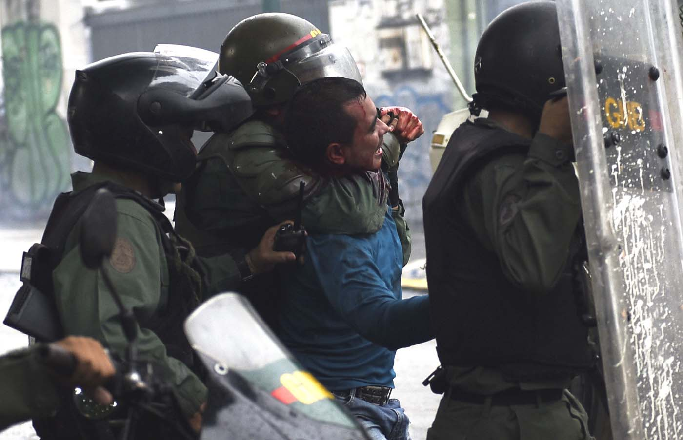 An anti-government activist is arrested during clashes in Caracas on July 28, 2017. Protesters took over streets in Caracas on Friday in a show of defiance to President Nicolas Maduro, as the crisis gripping Venezuela turned deadlier ahead of a controversial weekend election that has earned international scorn. / AFP PHOTO / CARLOS BECERRA