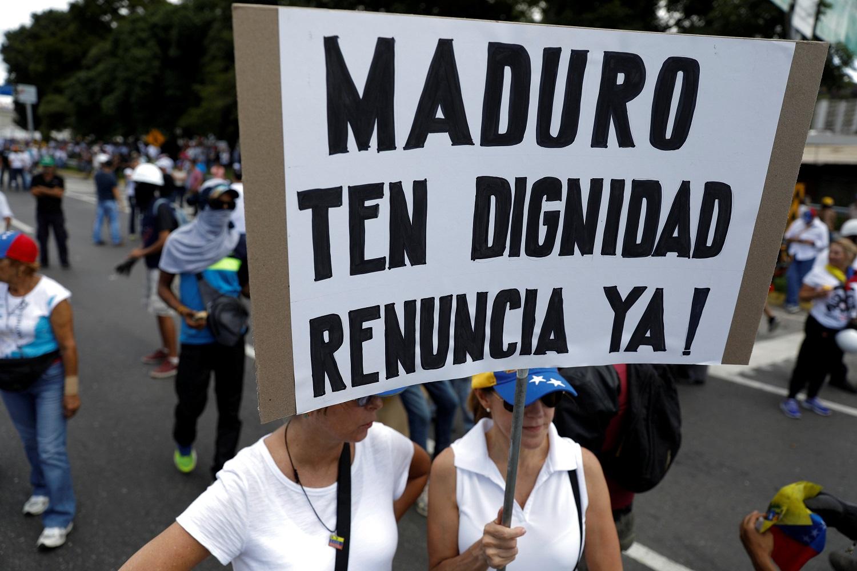 """Los partidarios de la oposición mantienen un cartel que dice """"¡Maduro, que tengan dignidad, renuncien ahora!"""", Durante una manifestación contra el gobierno del presidente venezolano, Nicolás Maduro, en Caracas, Venezuela el 1 de julio de 2017. REUTERS / Carlos Garcia Rawlins"""