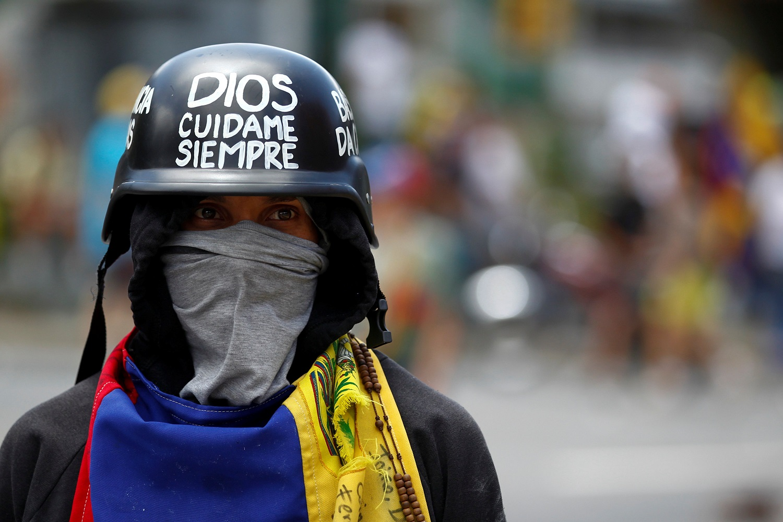 """Un manifestante que lleva un casco con el texto """"Dios, cuídame siempre"""" asiste a una manifestación contra el gobierno del presidente venezolano Nicolás Maduro en Caracas, Venezuela el 1 de julio de 2017. REUTERS / Christian Veron"""