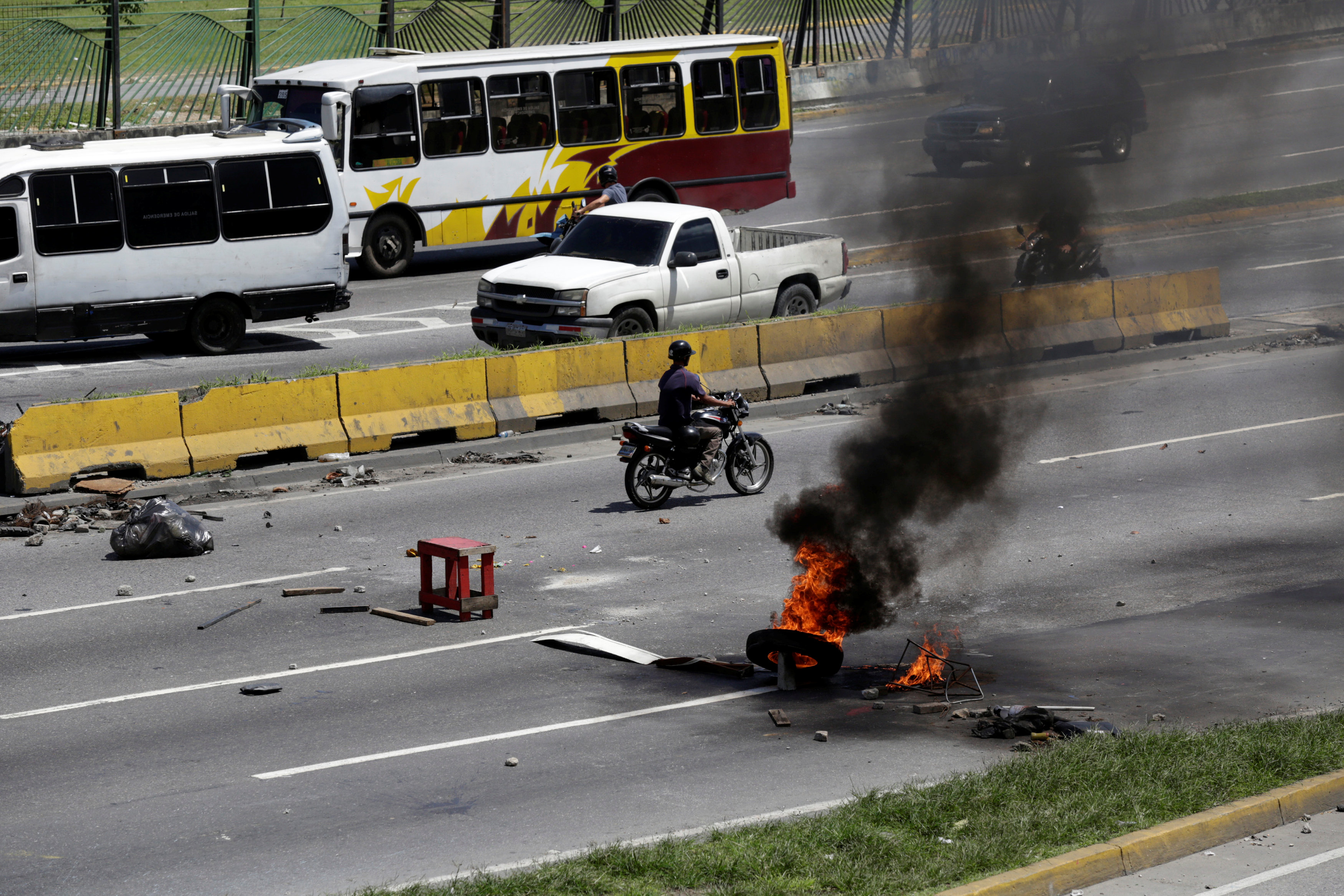 A man on a motorcycle rides near the remains of a fire barricade built by opposition supporters rallying against Venezuela's President Nicolas Maduro's government, in Caracas, Venezuela July 4, 2017. REUTERS/Marco Bello