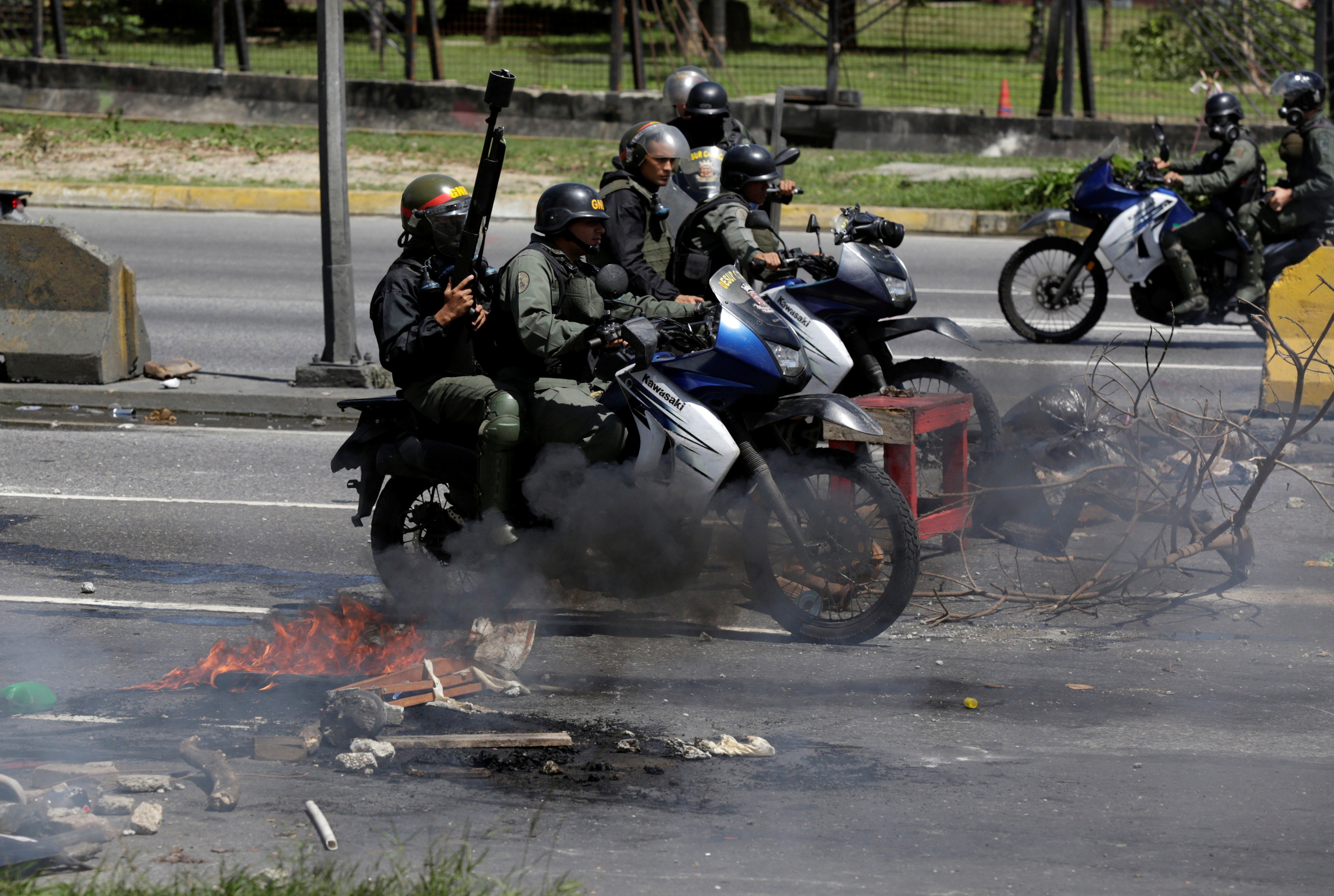 Riot security forces ride on their motorcycles past fire barricades built by opposition supporters rallying against Venezuela's President Nicolas Maduro's government, in Caracas, Venezuela July 4, 2017.  REUTERS/Marco Bello