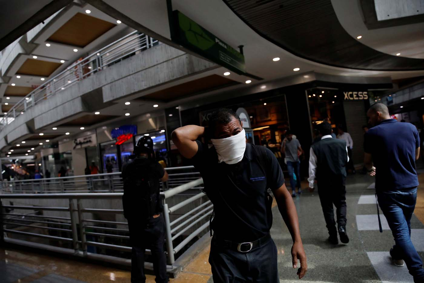 A man covers his face from tear gas inside a shopping mall as clashes between demonstrators and security forces occured on the streets during a rally against Venezuelan President Nicolas Maduro's government in Caracas, Venezuela, July 6, 2017. REUTERS/Carlos Garcia Rawlins