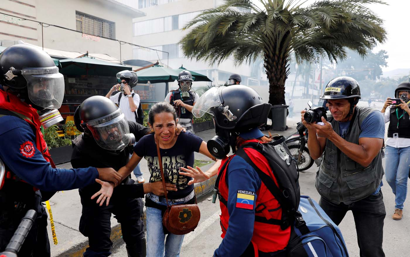 A woman is helped as she leaves a restaurant when smoke from tear gas fired by security forces got inside of it as clashes occured during a rally against Venezuelan President Nicolas Maduro's government in Caracas, Venezuela, July 6, 2017. REUTERS/Andres Martinez Casares