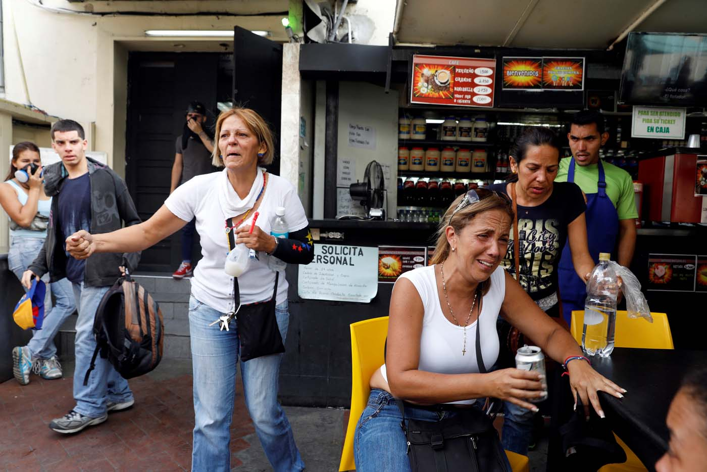 People react at a restaurant after smoke from tear gas fired by security forces got inside of it during clashes at a rally against Venezuelan President Nicolas Maduro's government in Caracas, Venezuela, July 6, 2017. REUTERS/Andres Martinez Casares