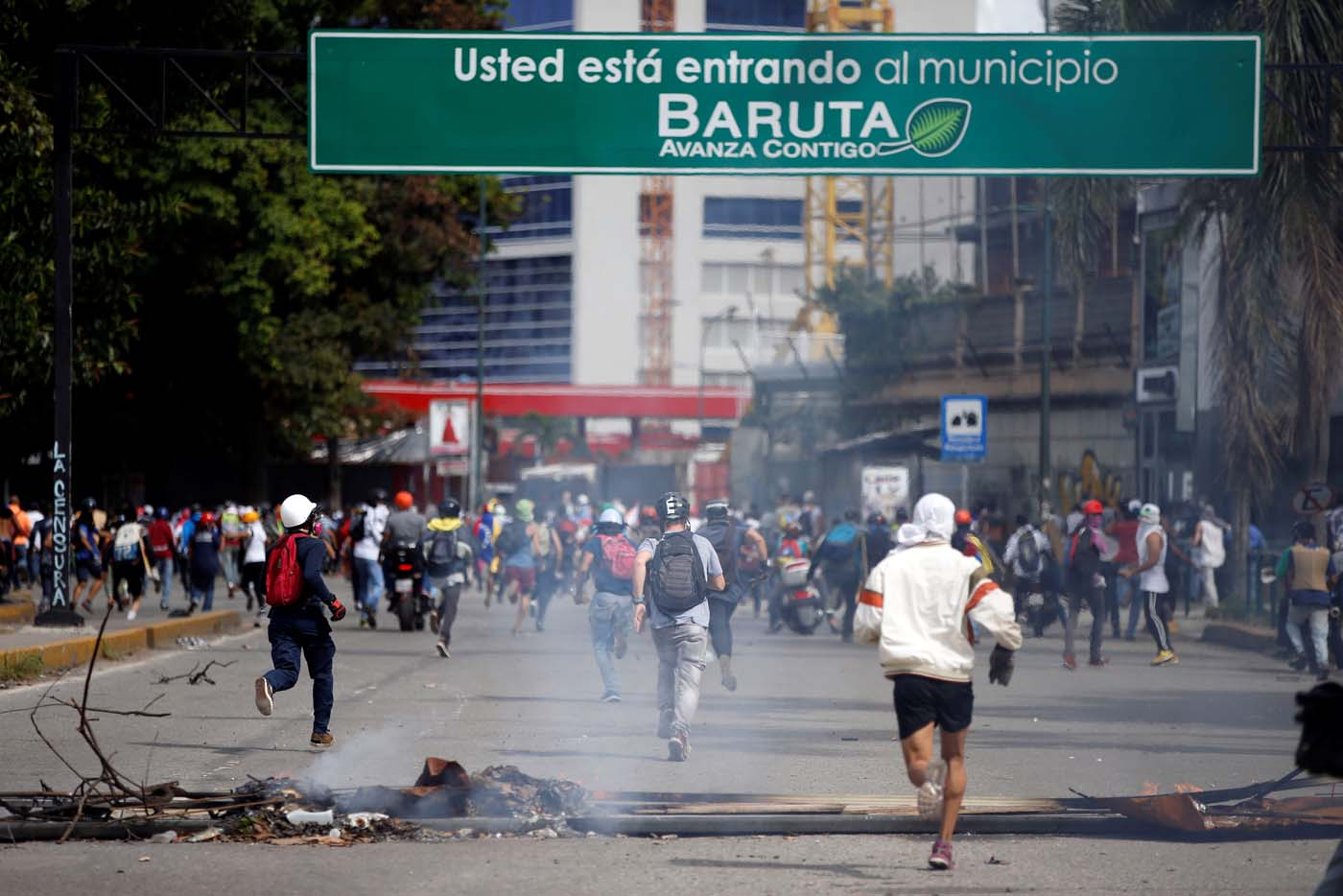 Demonstrators run past a barricade during clashes at a rally against Venezuelan President Nicolas Maduro's government in Caracas, Venezuela, July 6, 2017. REUTERS/Andres Martinez Casares