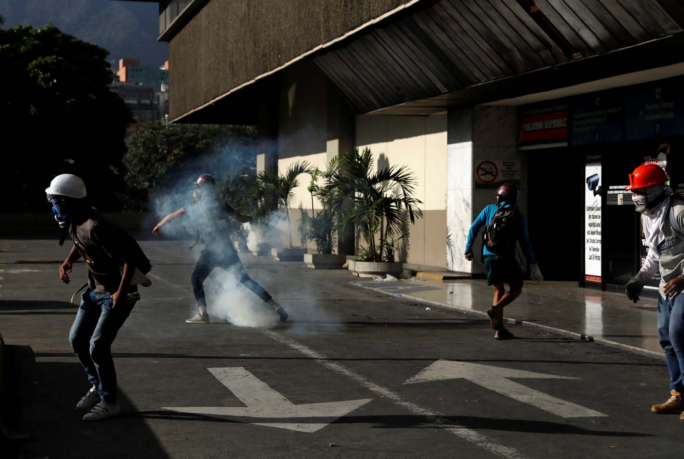 A demonstrator throws back a tear gas canister during clashes with security forces at a rally against Venezuelan President Nicolas Maduro's government in Caracas, Venezuela, July 6, 2017. REUTERS/Andres Martinez Casares