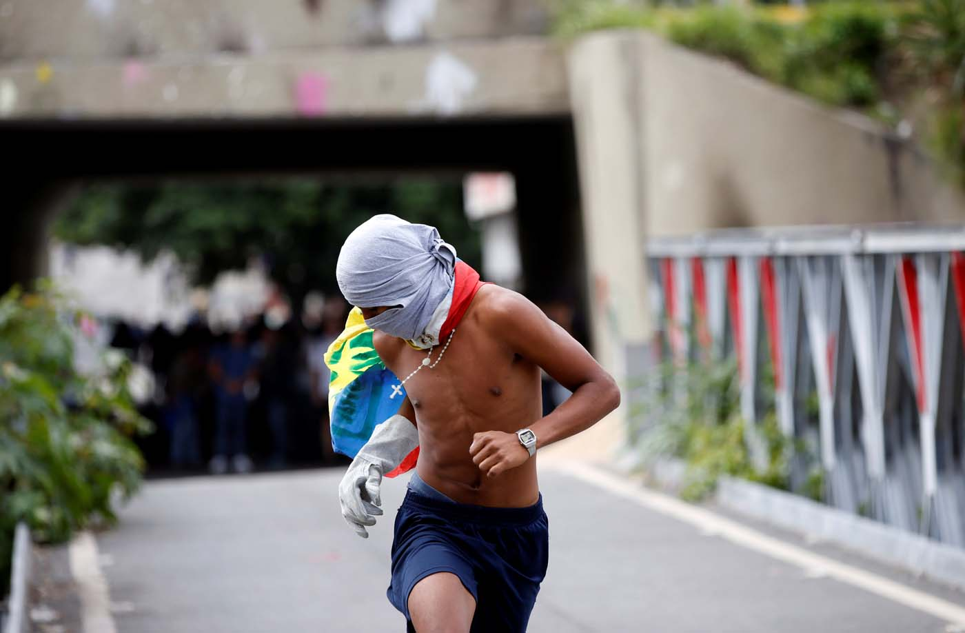 A masked demonstrator runs during clashes with security forces at a rally against Venezuelan President Nicolas Maduro's government in Caracas, Venezuela, July 6, 2017. REUTERS/Andres Martinez Casares