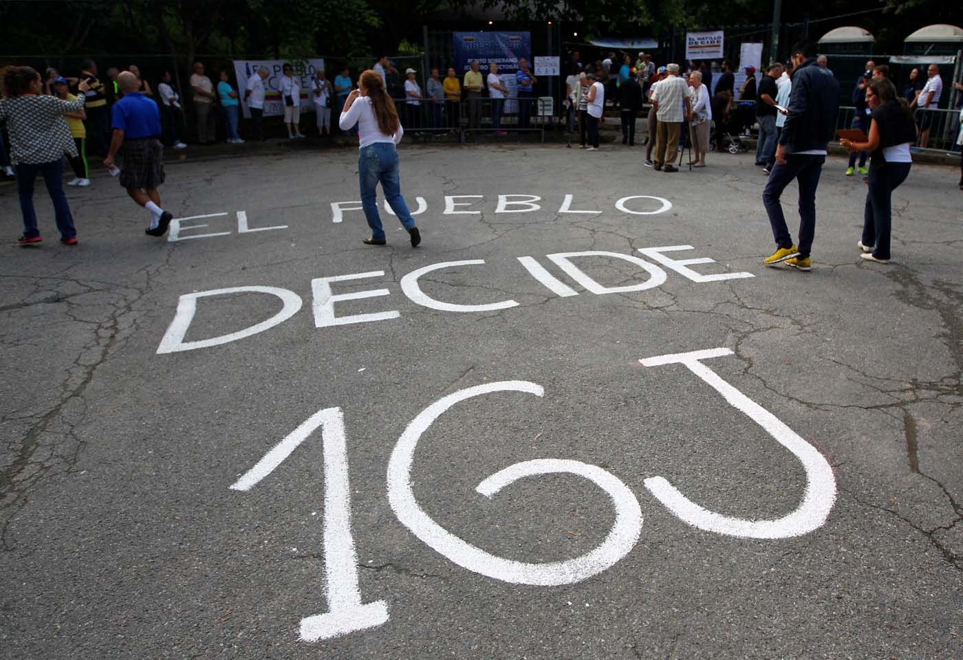 "People gather at a polling station during an unofficial plebiscite against Venezuela's President Nicolas Maduro's government and his plan to rewrite the constitution, in Caracas, Venezuela July 16, 2017. The writing on the pavement reads: ""The people decide 16J(uly)."" REUTERS/Christian Veron"