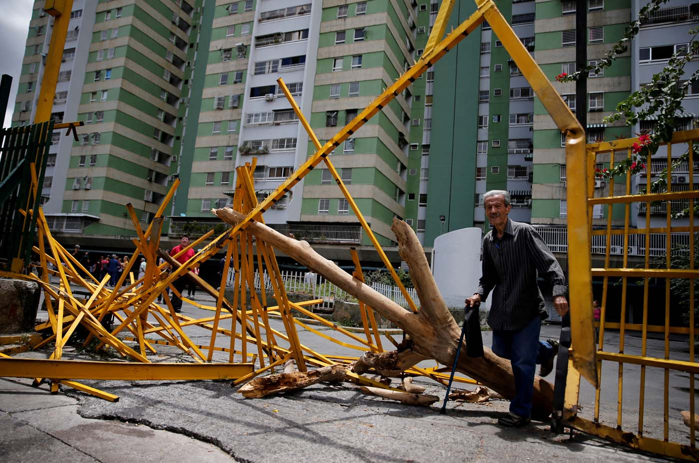 FILE PHOTO: A man walks through a broken main gate after opposition supporters and security forces clashed in and outside residential buildings on Tuesday according to residents, in Caracas, Venezuela June 14, 2017. REUTERS/Ivan Alvarado/File Photo