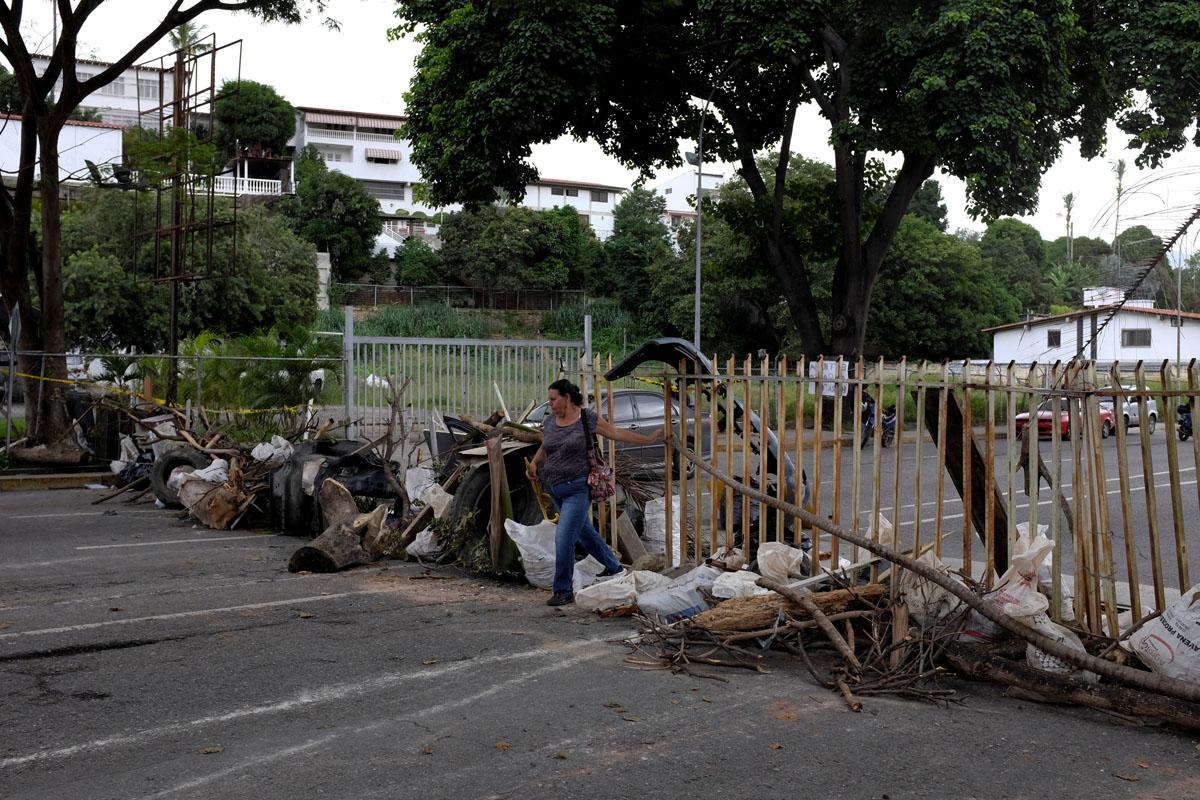Pedestrians walk past a barricade during a rally against Venezuelan President Nicolas Maduro's government in Caracas, Venezuela July 19, 2017. REUTERS/Marco Bello