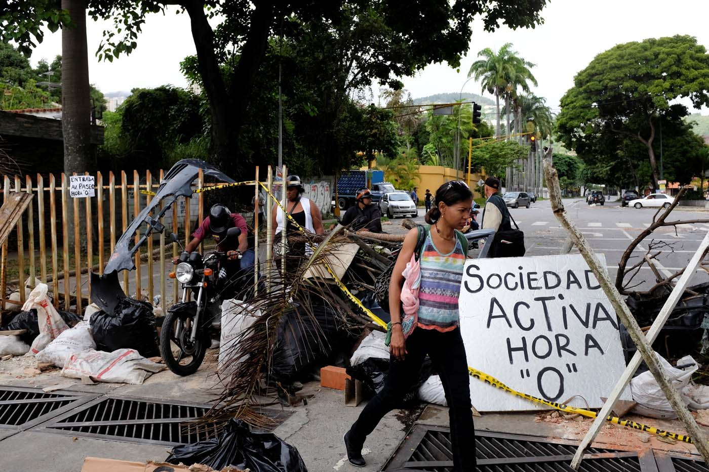"""Pedestrians walk past a barricade during a rally against Venezuelan President Nicolas Maduro's government in Caracas, Venezuela July 19, 2017. The placard reads, """"Active society. Hour 0"""". REUTERS/Marco Bello"""