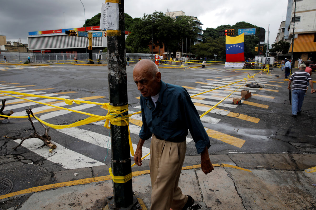 A pedestrian walks past a barricade during a rally against Venezuelan President Nicolas Maduro's government in Caracas, Venezuela, July 19, 2017.  REUTERS/Carlos Garcia Rawlins